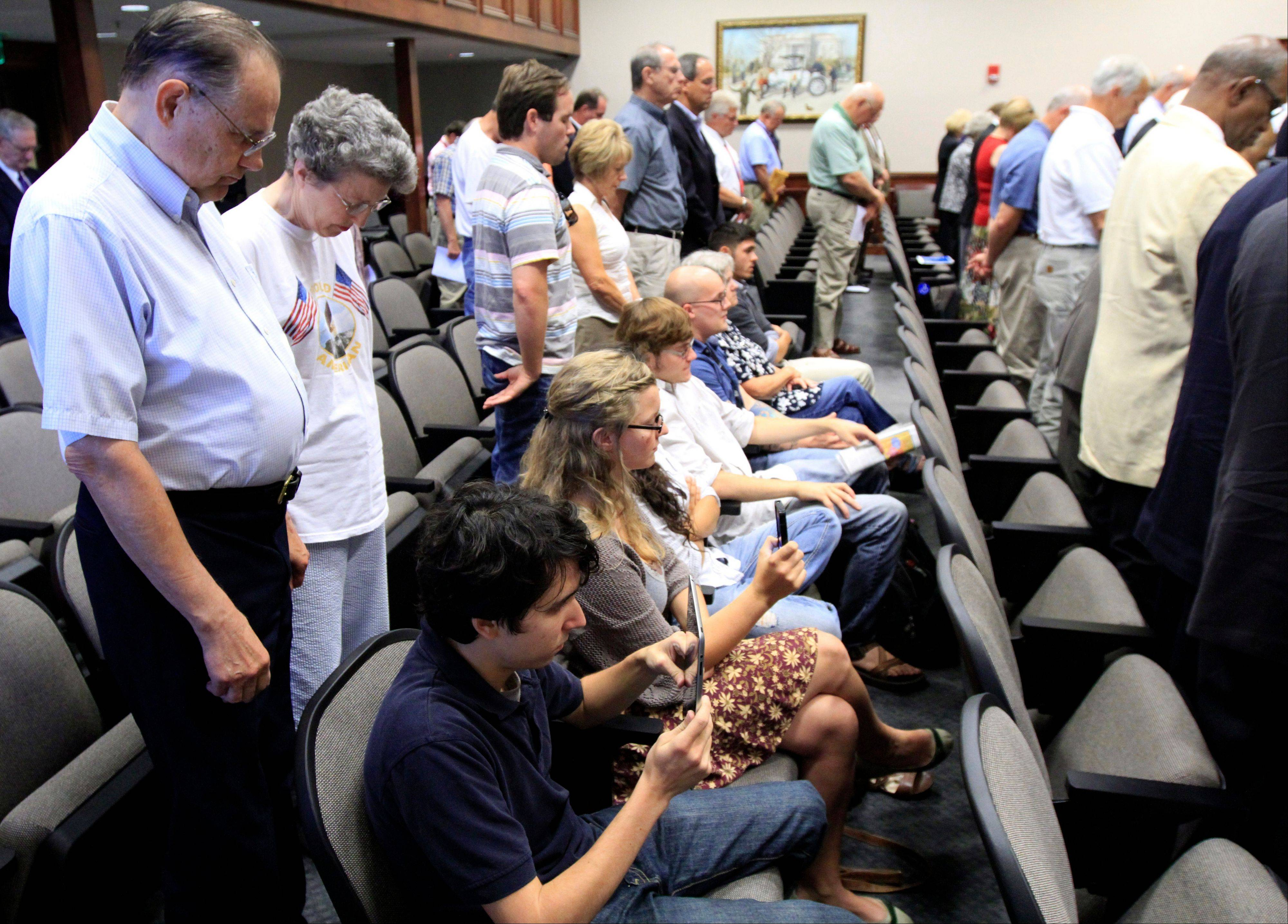 Protesters remain seated during an opening prayer during Hamilton County Commission meeting in Chattanooga, Tenn.