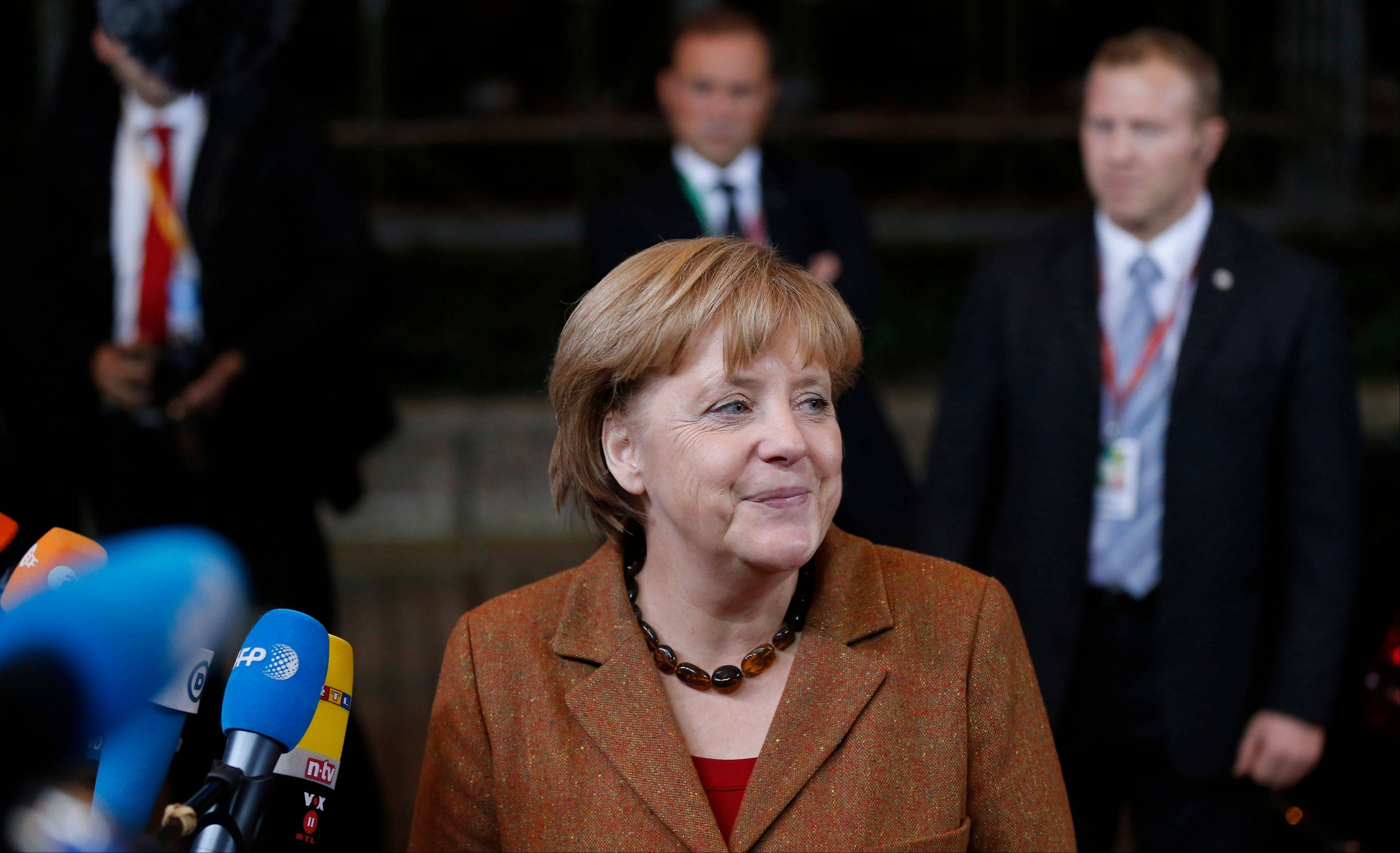 German Chancellor Angela Merkel, center, speaks with the media as she arrives for an EU summit at the EU Council building in Brussels on Thursday. EU leaders begin what is expected to be a marathon summit on the budget for the years 2014-2020. The meeting could last through Saturday and break up with no result and lots of finger-pointing.