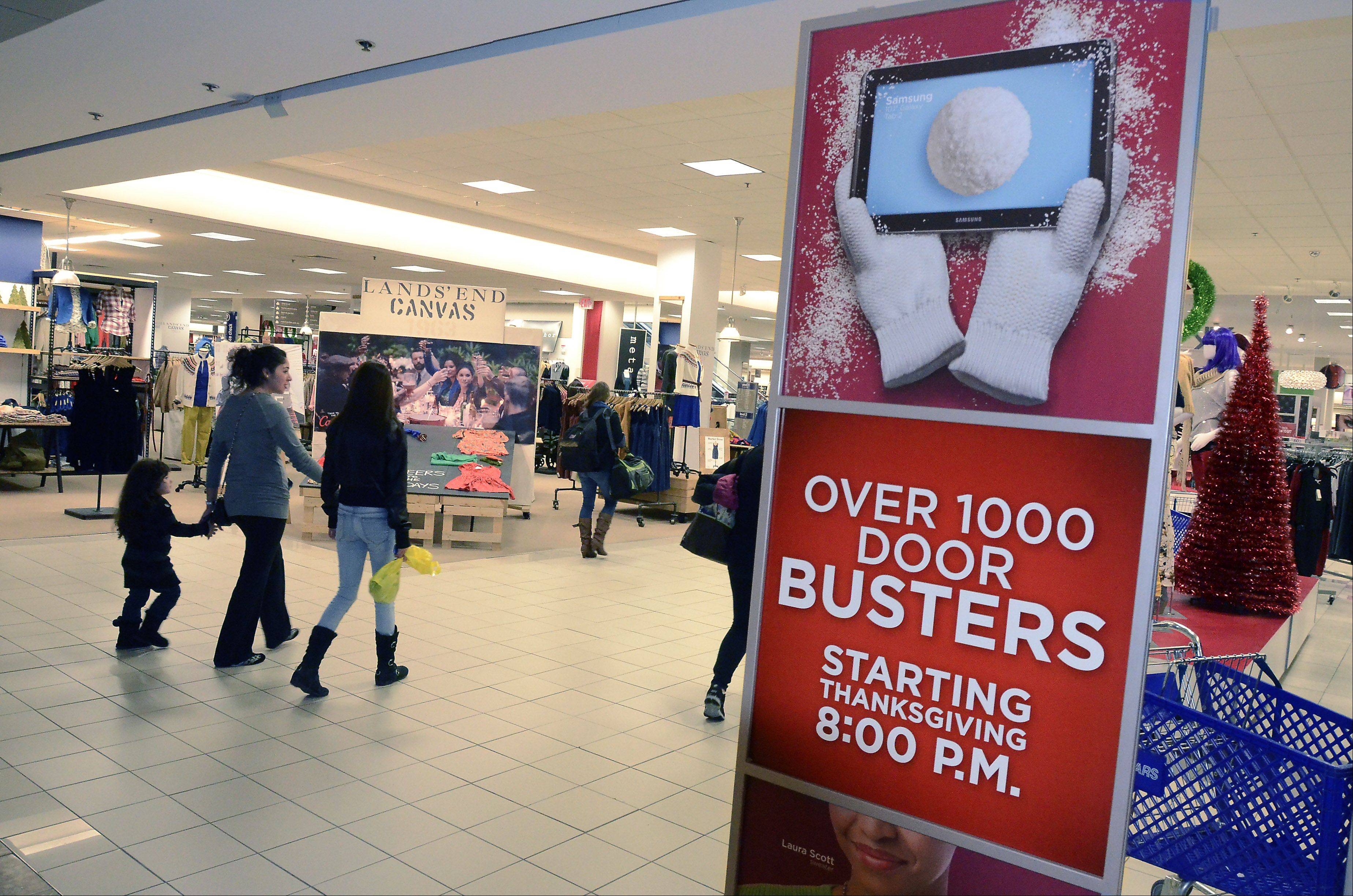 Signs at Sears in Woodfield Mall urge shoppers to start shopping for Black Friday deals before their turkey dinner is digested. Sears is one of several national retailers starting Black Friday sales at 8 p.m. on Thanksgiving this year.
