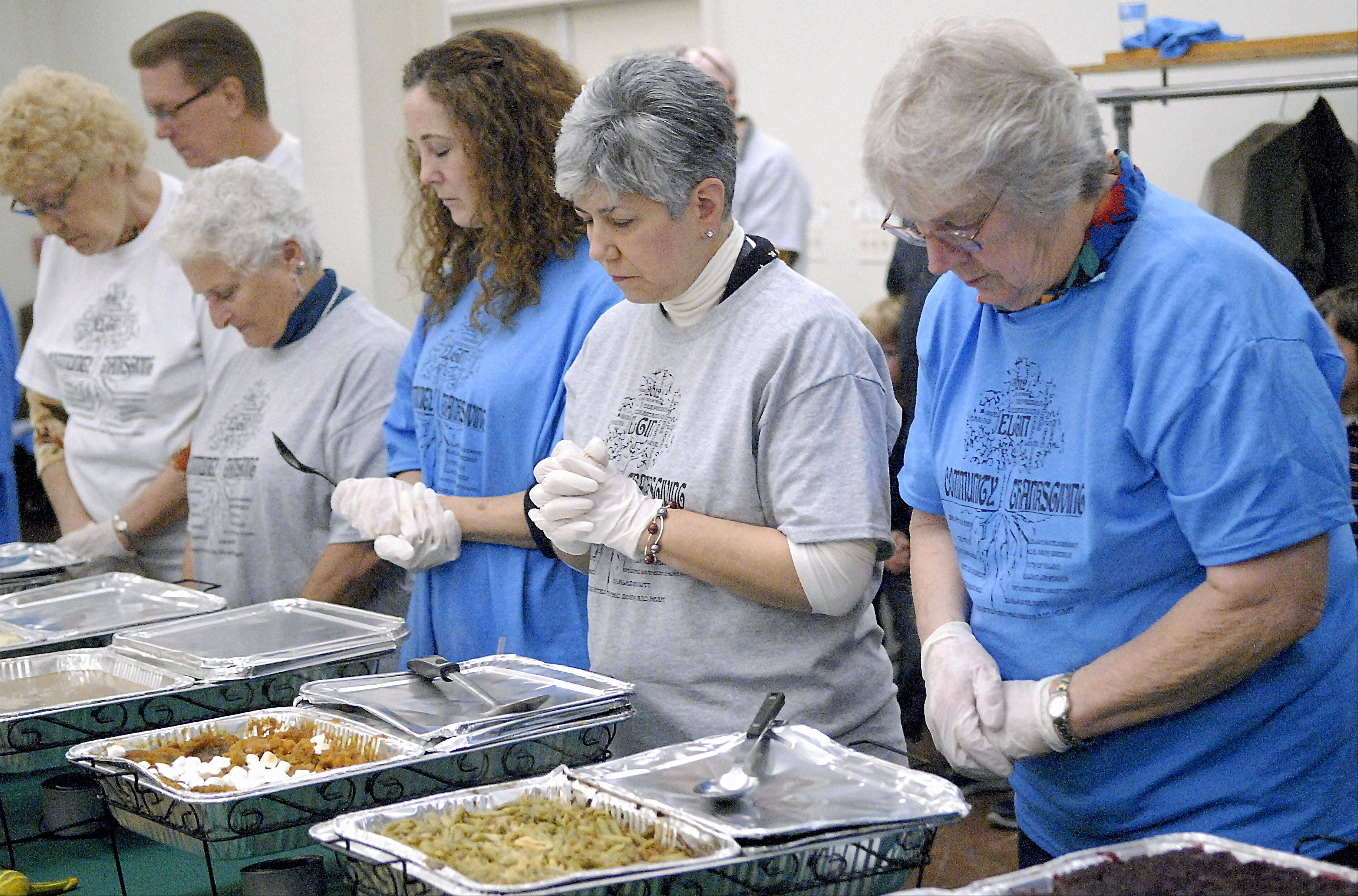 Beth Anderson of Streamwood, third from left, Carol Johnson and Marlene Hensrud, both of Elgin, bow their heads in prayer with fellow volunteers before serving at the fourth annual community dinner at First United Methodist Church in Elgin on Thursday. Johnson and Hensrud are residents of the Edgewood active adult community in Elgin, and they brought several volunteers to help out again this year.