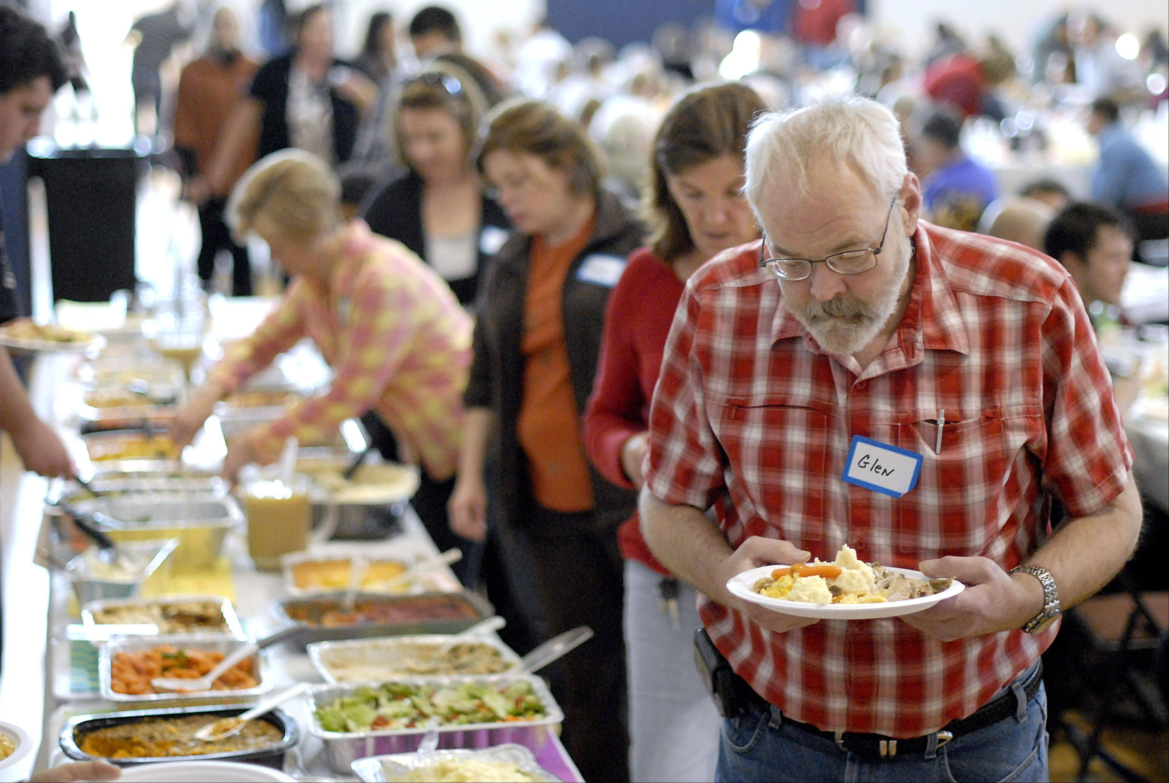 Glen Ostgaard of Geneva fills a plate at Lazarus House's annual Thanksgiving Day dinner at the Salvation Army in St. Charles. Ostgaard has been coming to the dinner for the last several years.