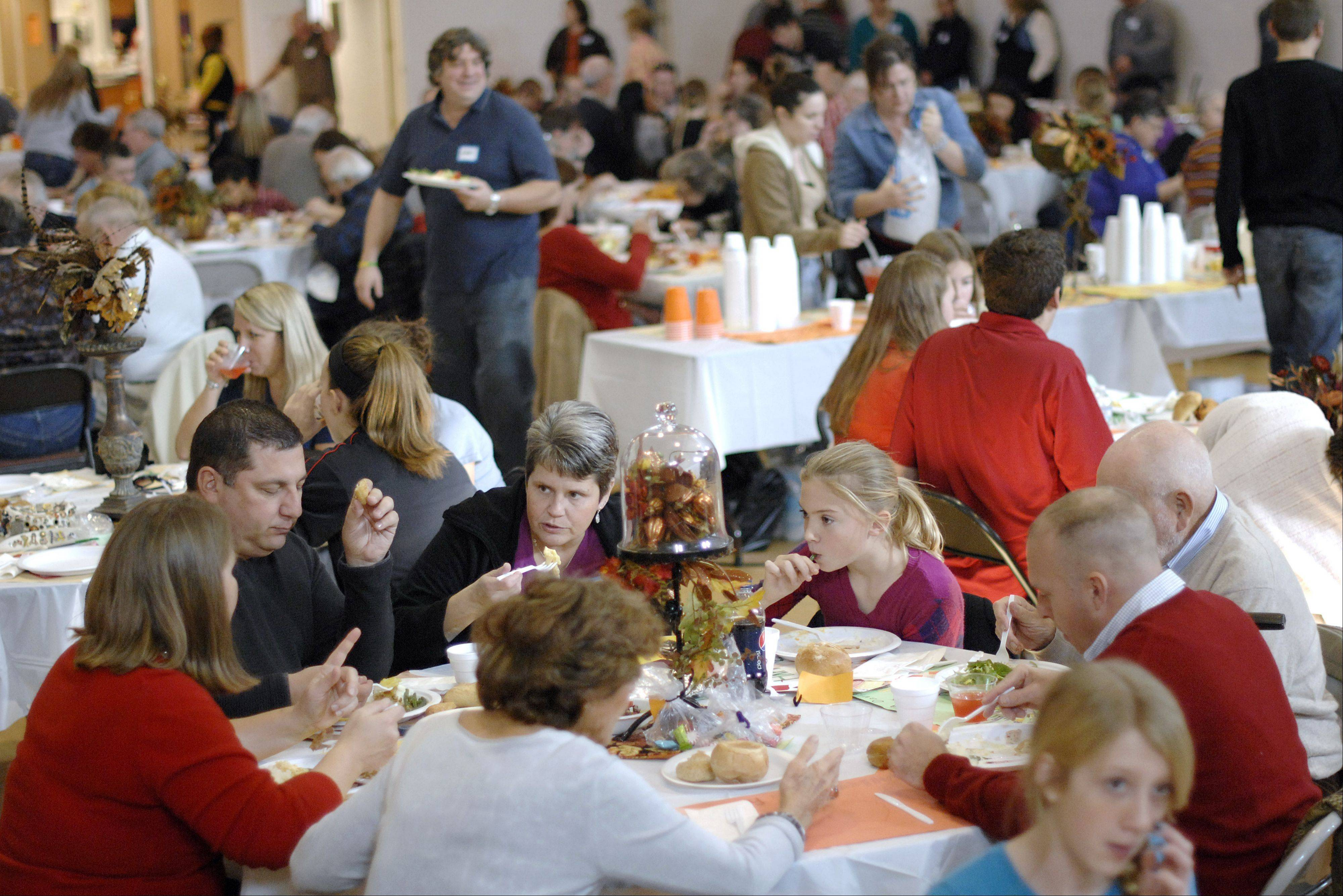 Families dine at the annual Thanksgiving Day dinner hosted by Lazarus House at the Salvation Army in St. Charles.