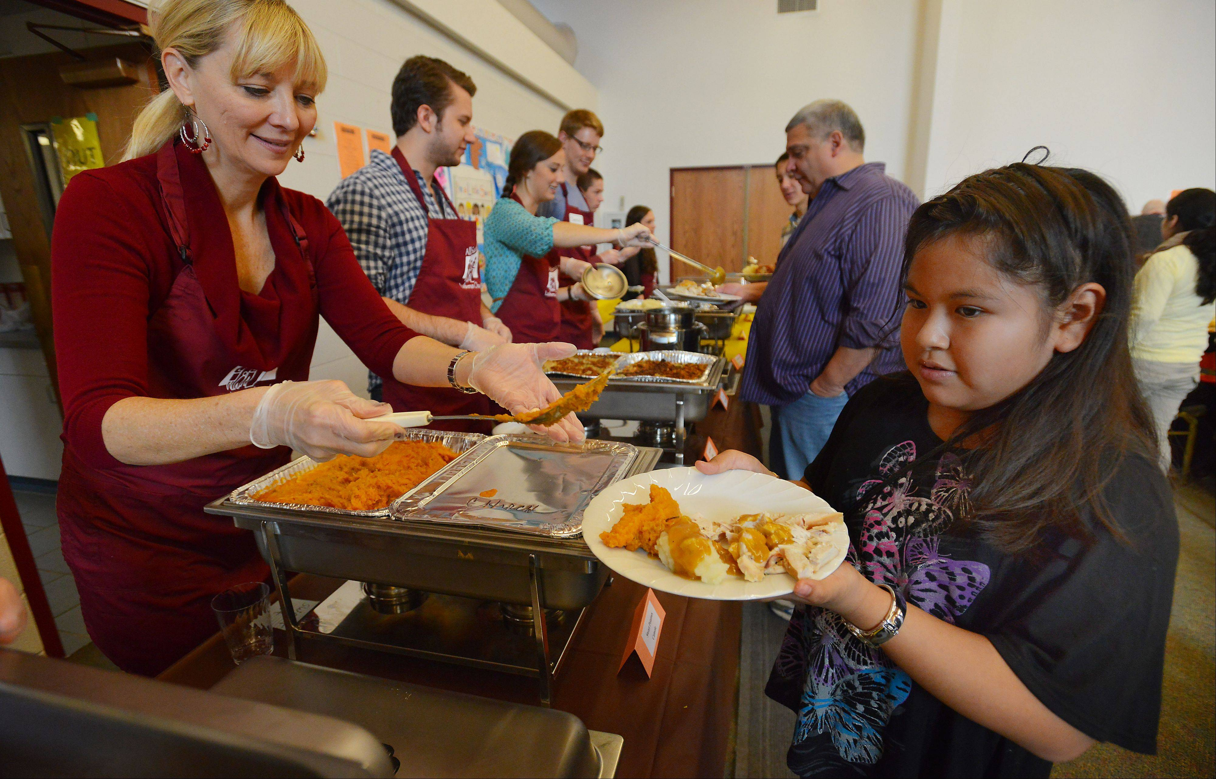 Church volunteer Dee Gray of Palatine serves up a hot turkey dinner to Yenice Benitez,11, of Rolling Meadows at the All Saints Lutheran Church on Thanksgiving Day.