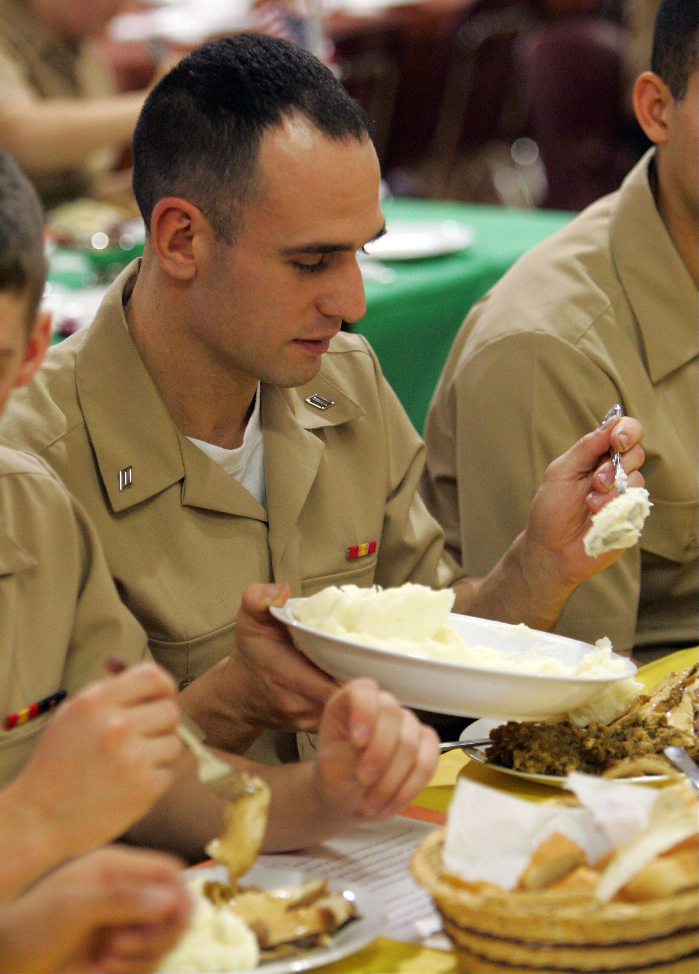 Seaman Recruit Gur Yilmaz of Newark, New Jersey serves himself some mashed potatoes as the Gurnee Community Church hosted 182 sailors from Recruit Training Command, Great Lakes for their 10th annual Thanksgiving Day feast.