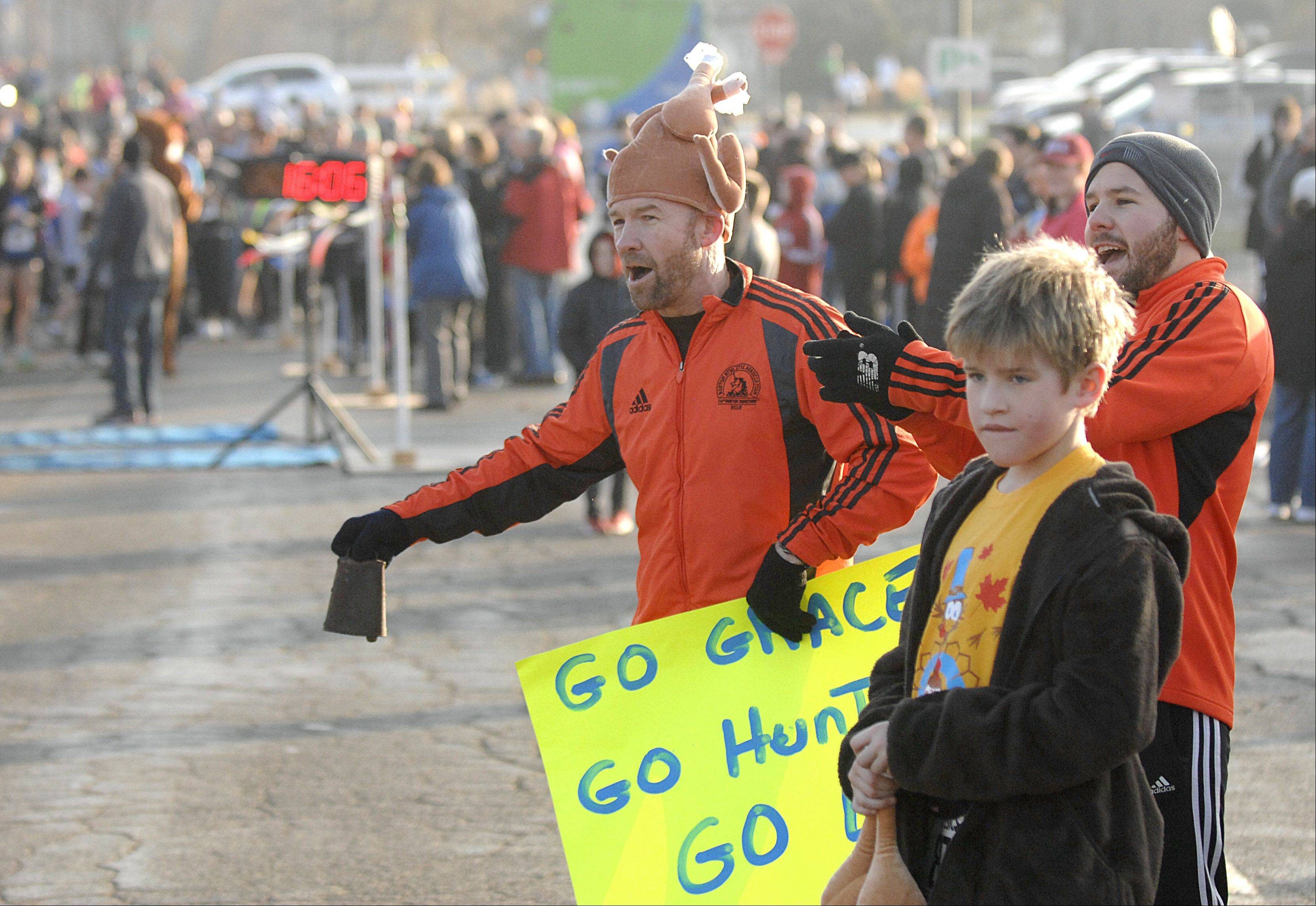 Jim Webb of St. Charles cheers runners in the youth division as they near the finish line at the 16th annual Fox & Turkey 4-mile run in Batavia on Thanksgiving Day.