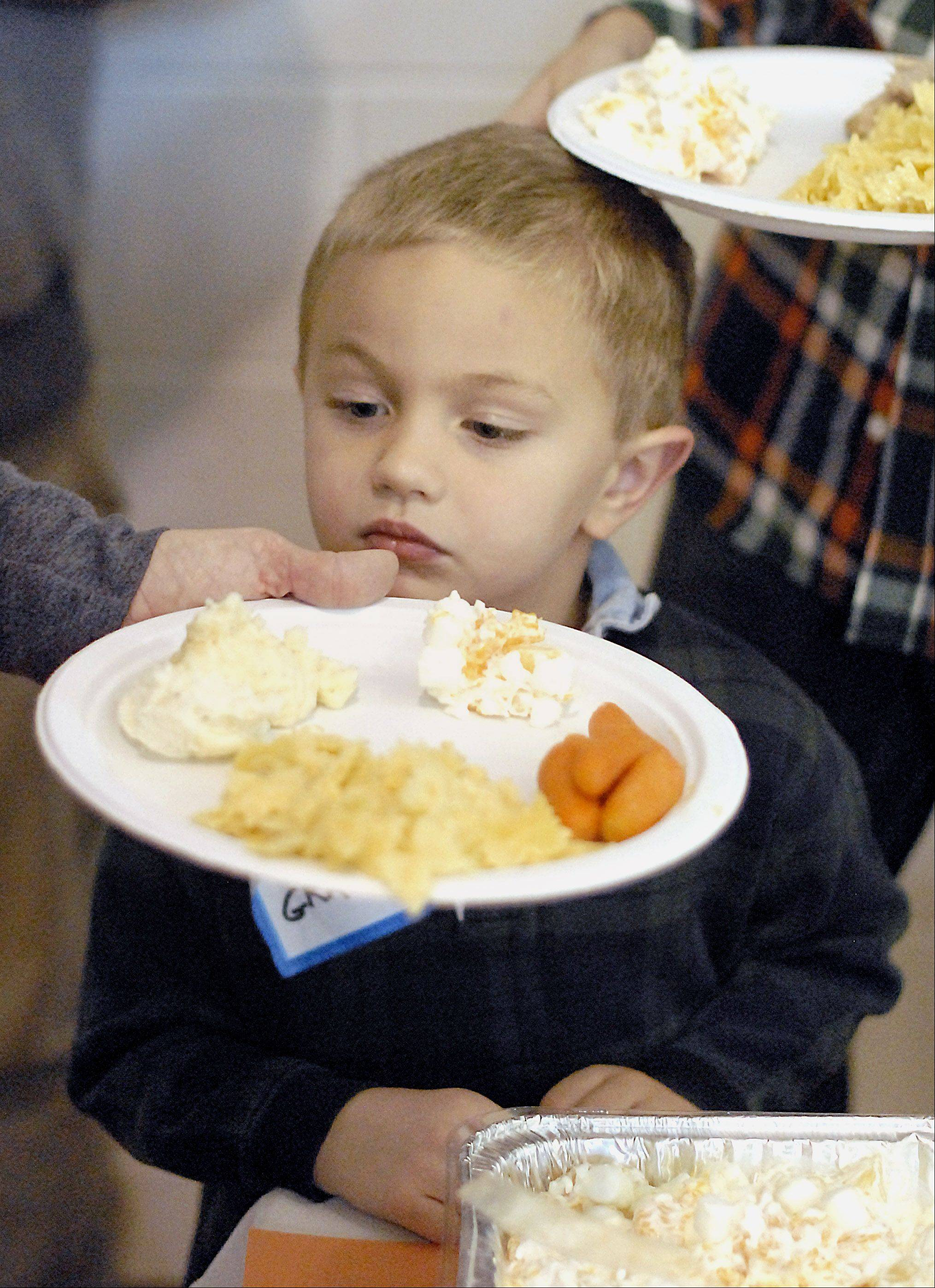 Grady Babcock, 4, of St. Charles watches at his mom, Jill, fills up his plate Lazarus House's annual Thanksgiving Day dinner at the Salvation Army in St. Charles. Members of the Babcock family have been attending the meal for the past seven years.