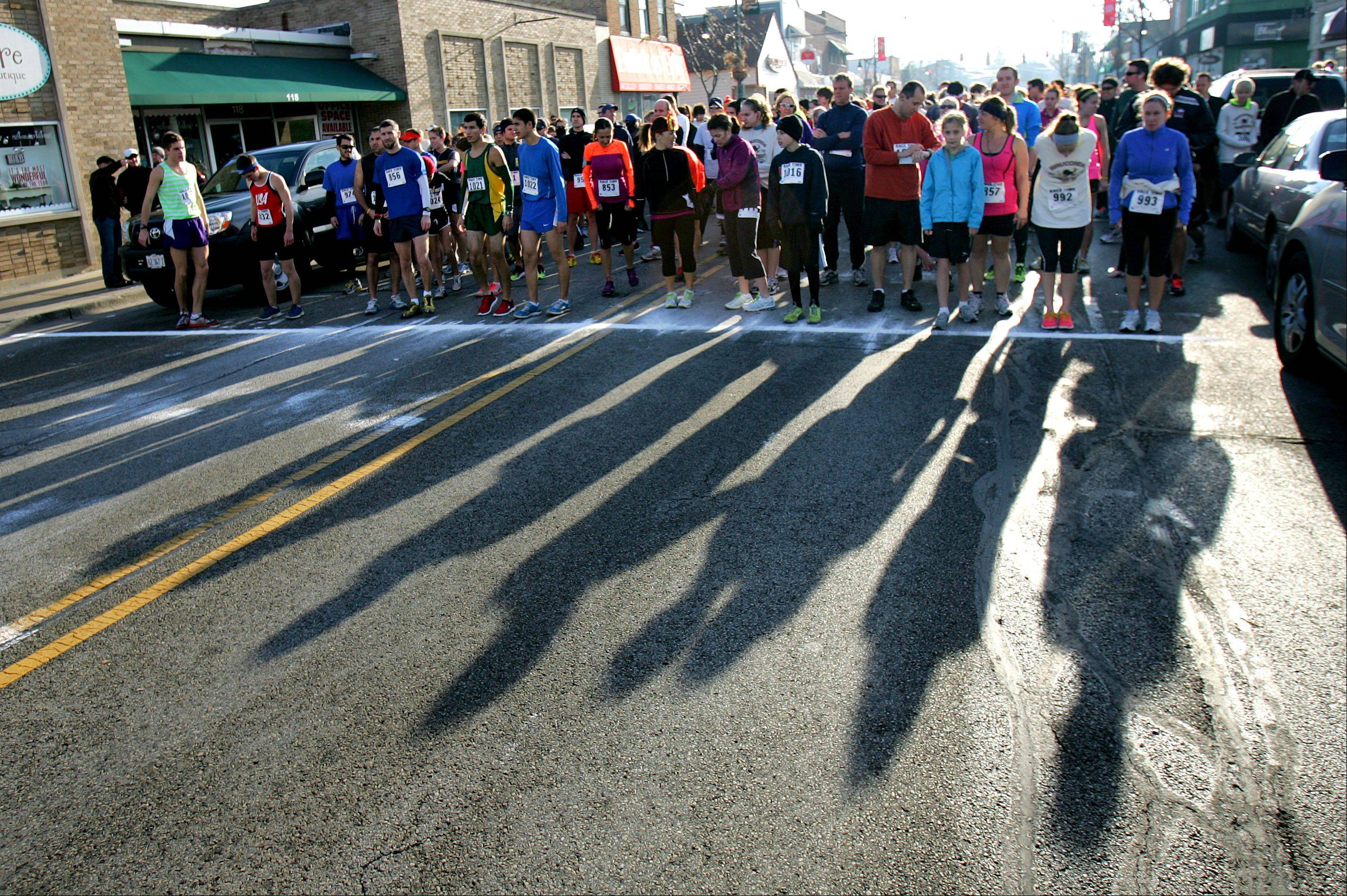 Morning shadows stretch down Main St. in downtown Wauconda as runners prepare for second annual Wauconda Turkey Trot.