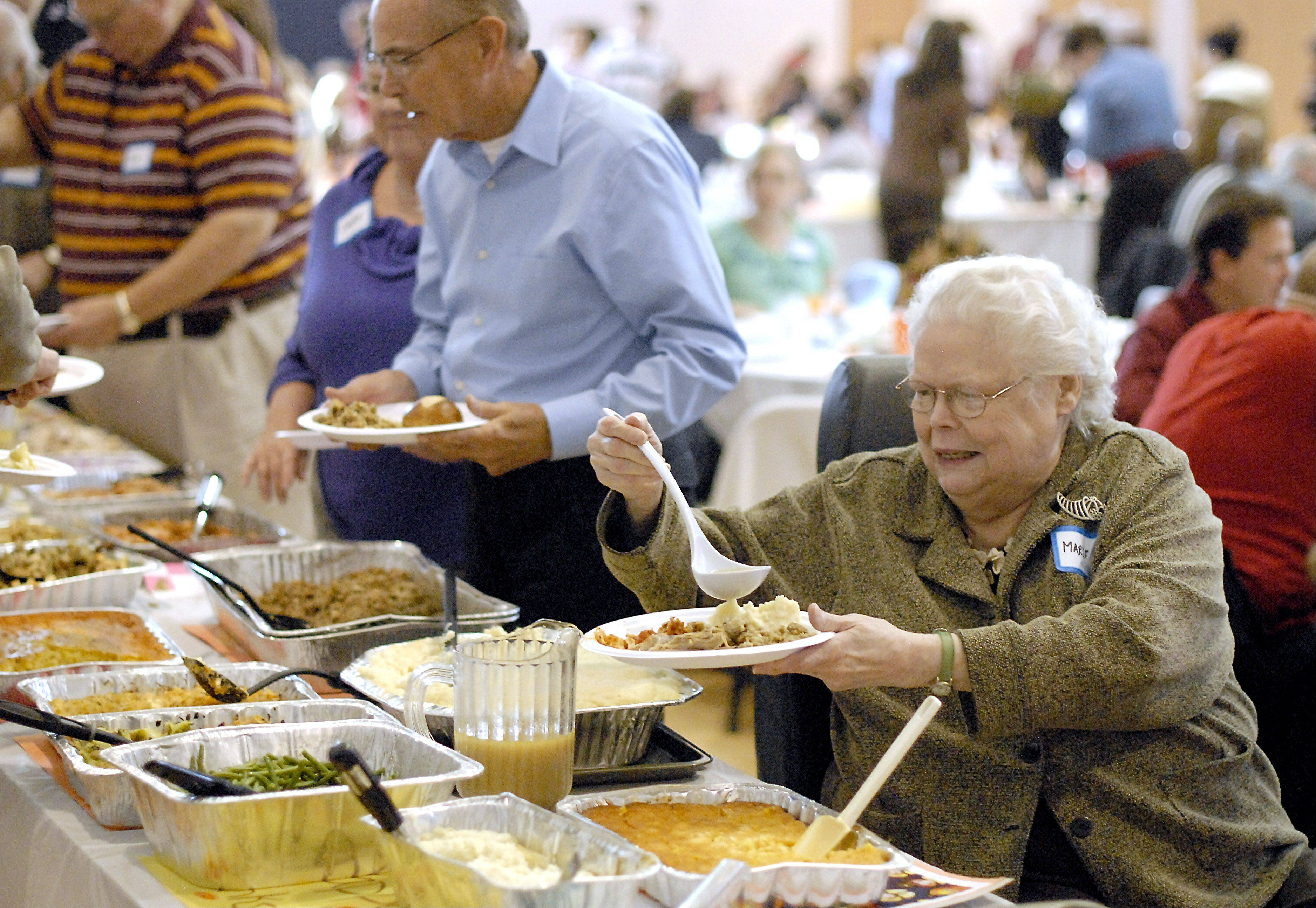 Marlene Thanepohn of St. Charles fills her plate at Lazarus House's annual Thanksgiving Day dinner at the Salvation Army in St. Charles. Thanepohn came by herself. After spending the past four years alone, she decided to come to the community dinner.