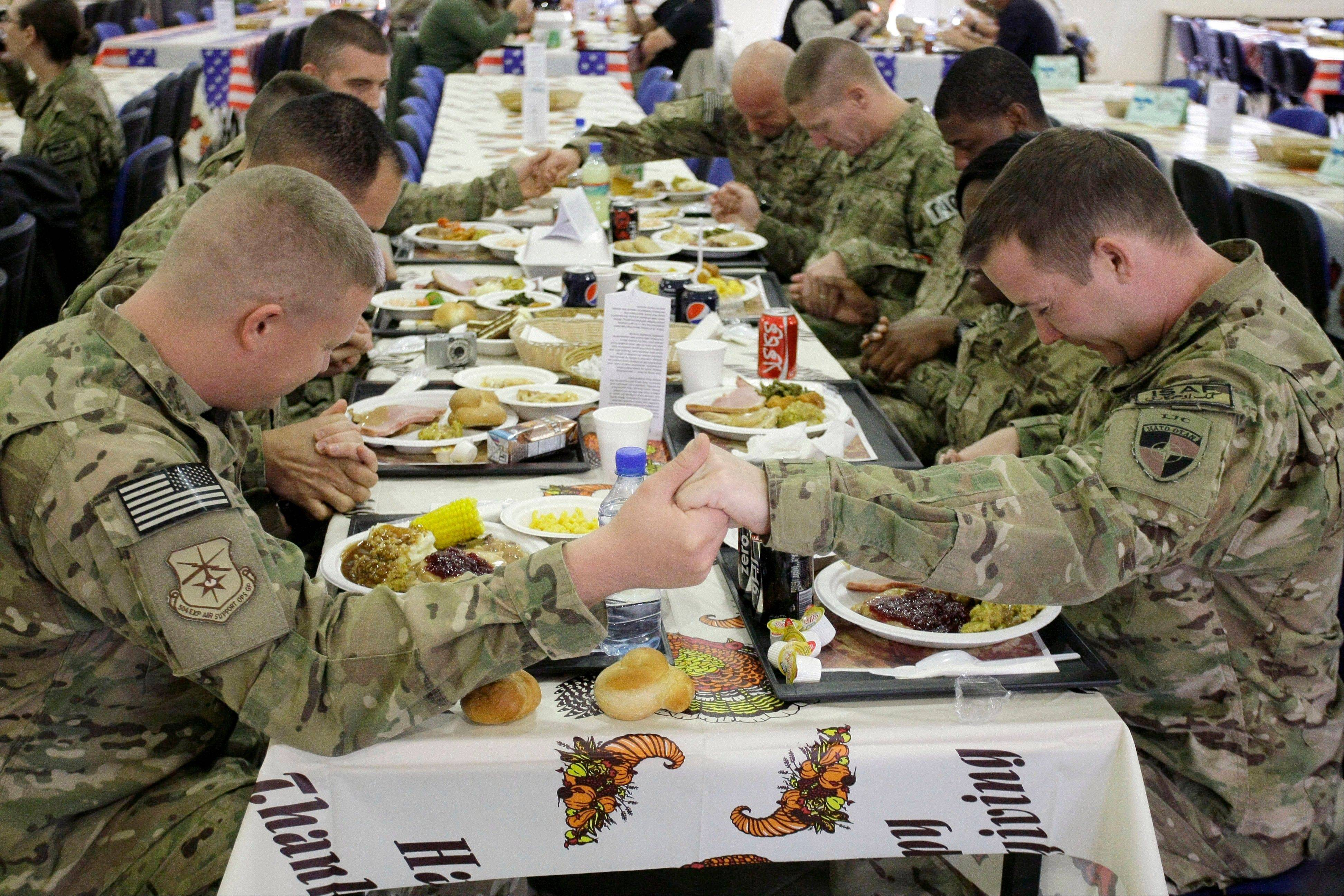 U.S. soldiers pray before eating a Thanksgiving meal at a dining hall at the U.S.-led coalition base in Kabul, Afghanistan, Thursday, Nov. 22, 2012. The dining hall at the U.S.-led coalition base in the Afghan capital served up mac-and-cheese along with traditional Thanksgiving Day fixings.