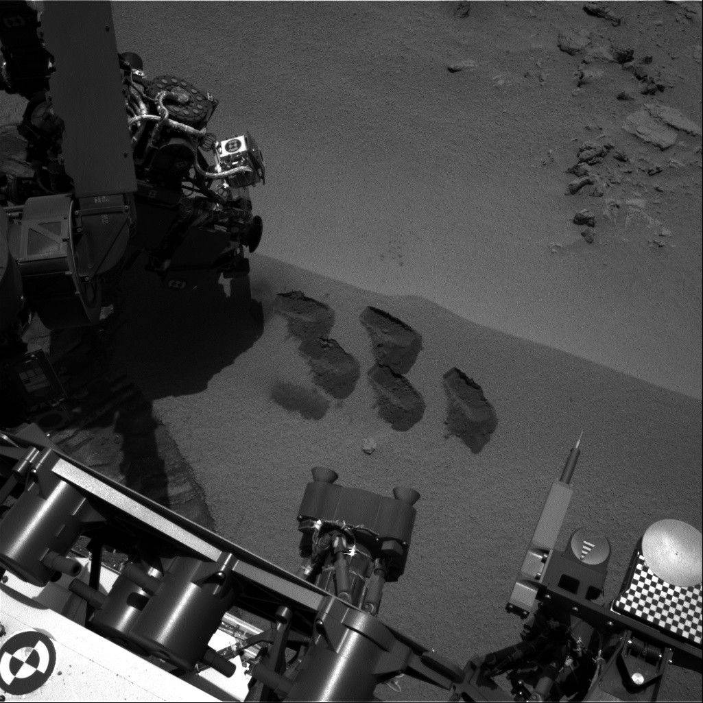 This image by NASA shows marks in the Martian soil made by the rover Curiosity. The space agency said the six-wheel rover is set to drive to a new destination soon. It landed in August on a two-year mission to study whether the environment is suitable for microbial life.