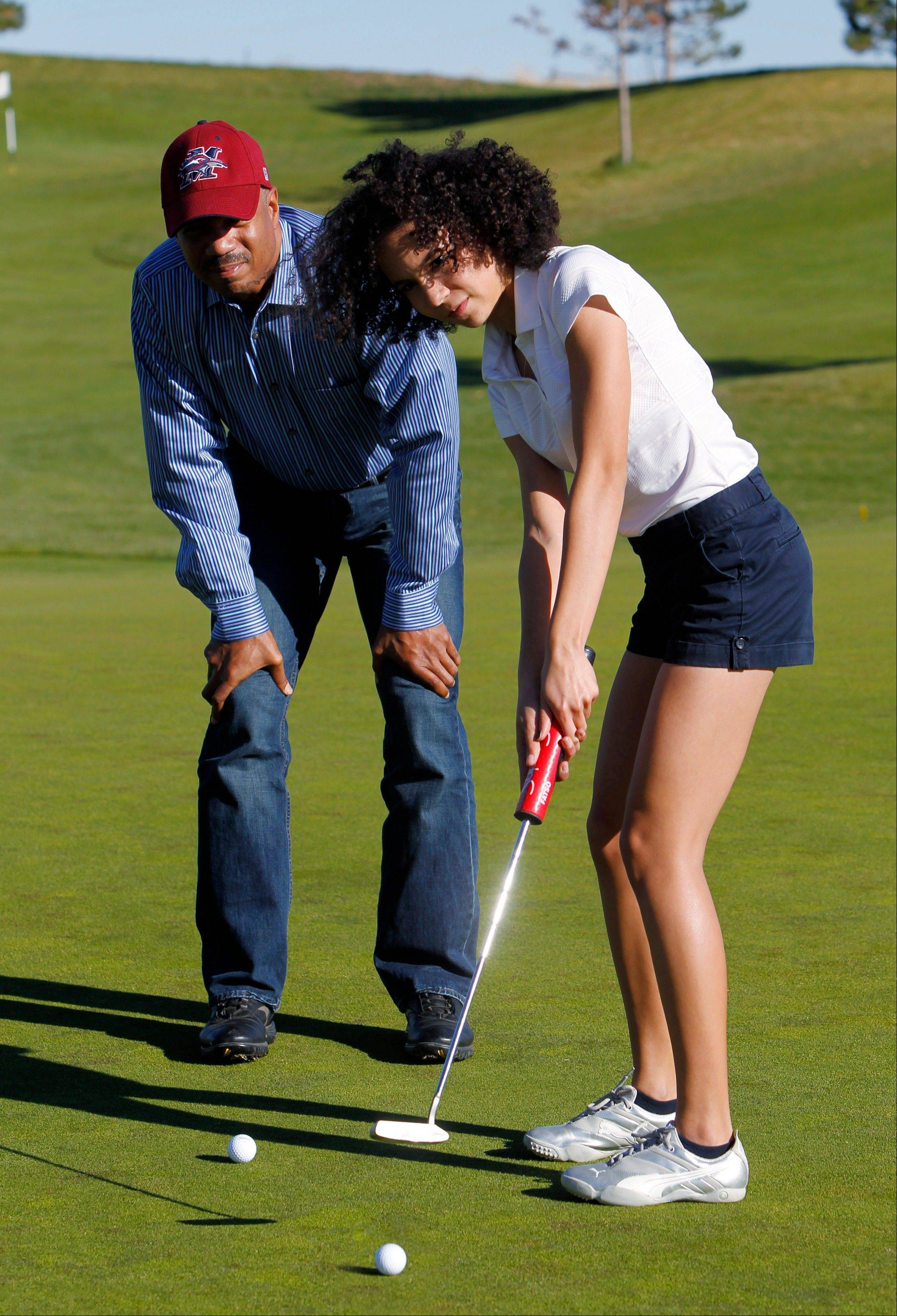 Shawn Worthy watches as his 16-year-old daughter Soleil practices putting at a golf course near their home in Aurora, Colo. Worthy, a professor at Metropolitan State University of Denver with an interest in sports psychology, questions the extreme emphasis that parents put on youth in sports.