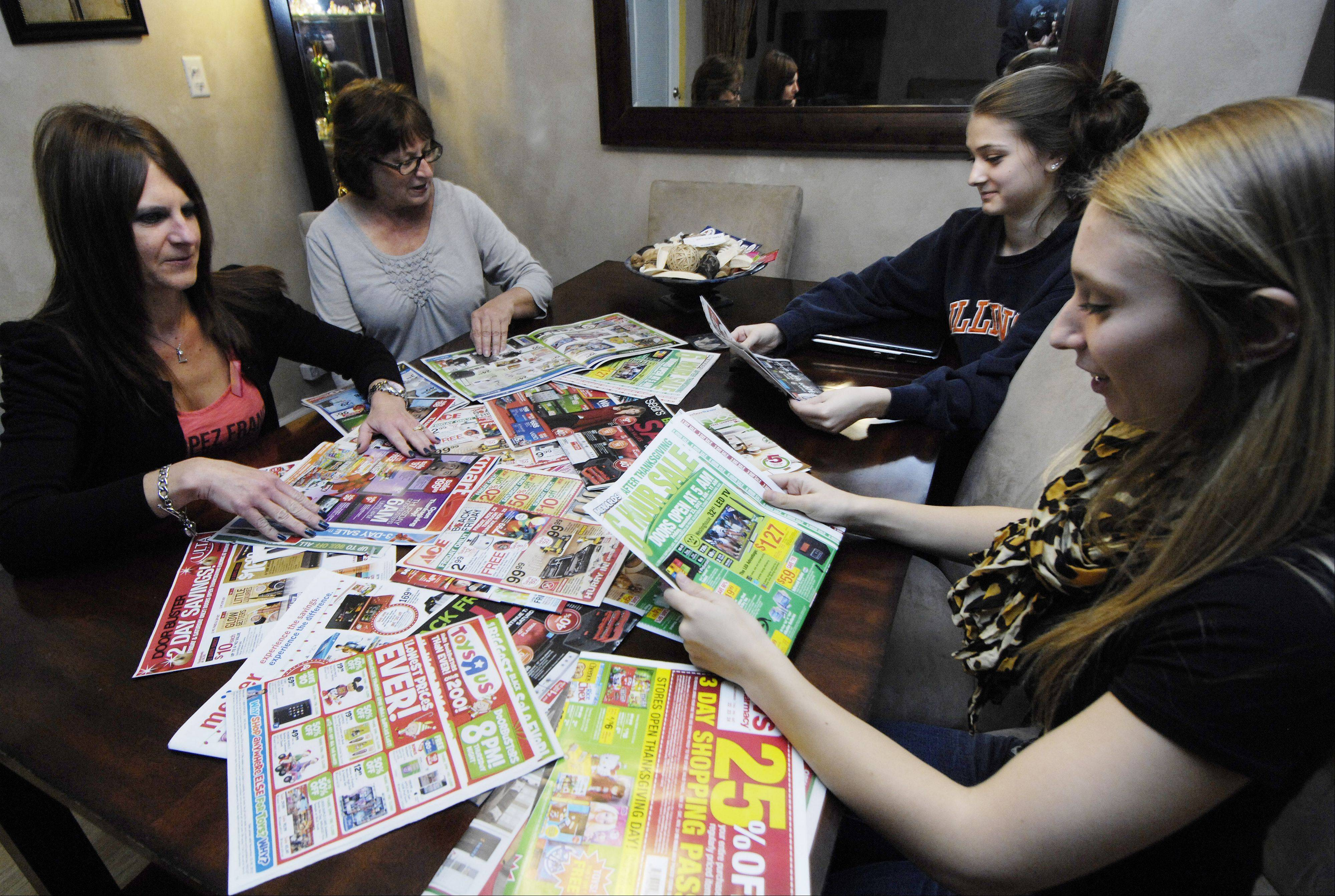 Clockwise from left, Laura Milman of Mount Prospect, her mom, Marge Grudzien of Niles, and her nieces Taylor and Natasha Tsinonis of Des Plaines go through the Black Friday ads in preparation for the big shopping day.