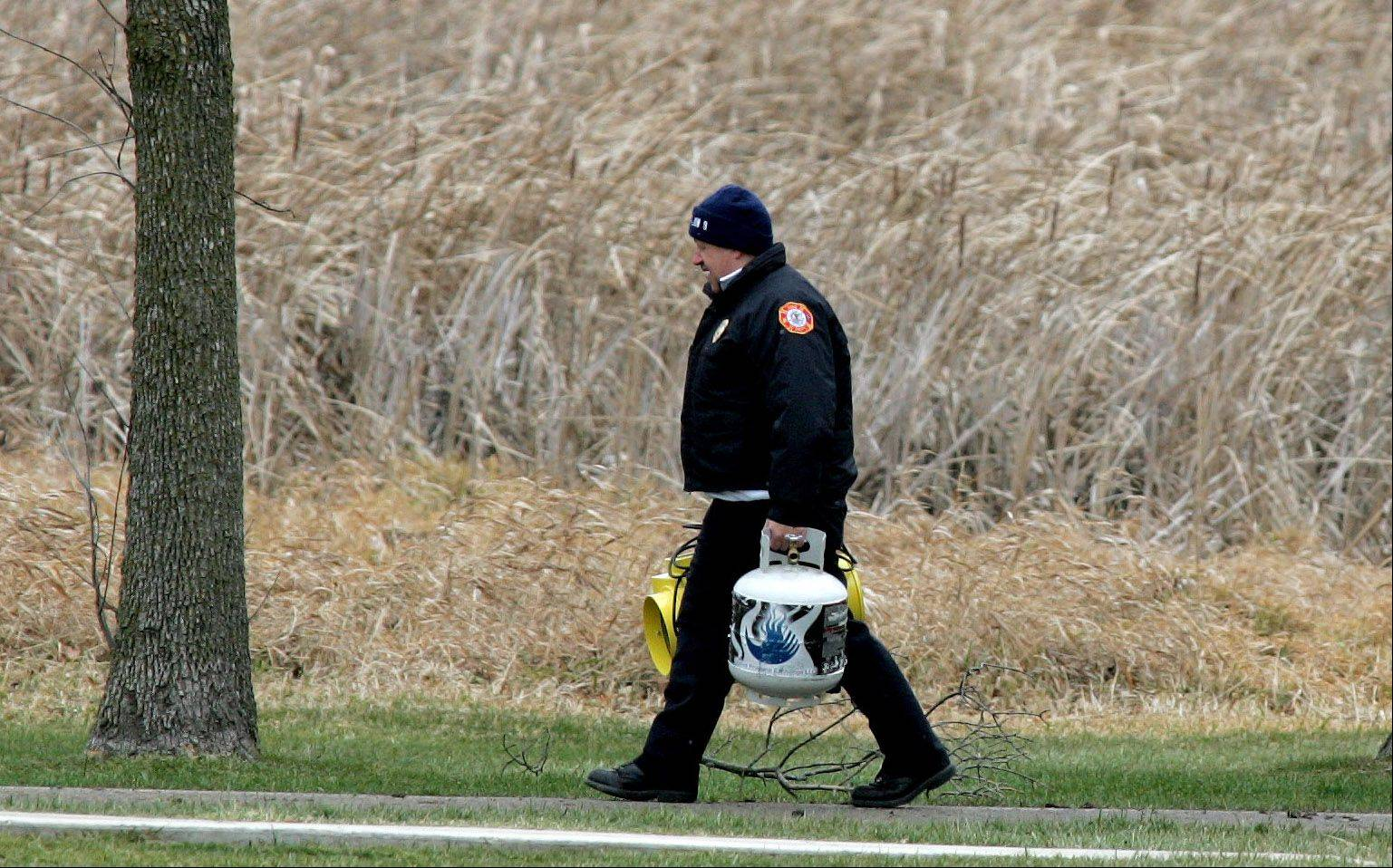 Investigators carry equipment into Shady Oaks Park Friday morning.