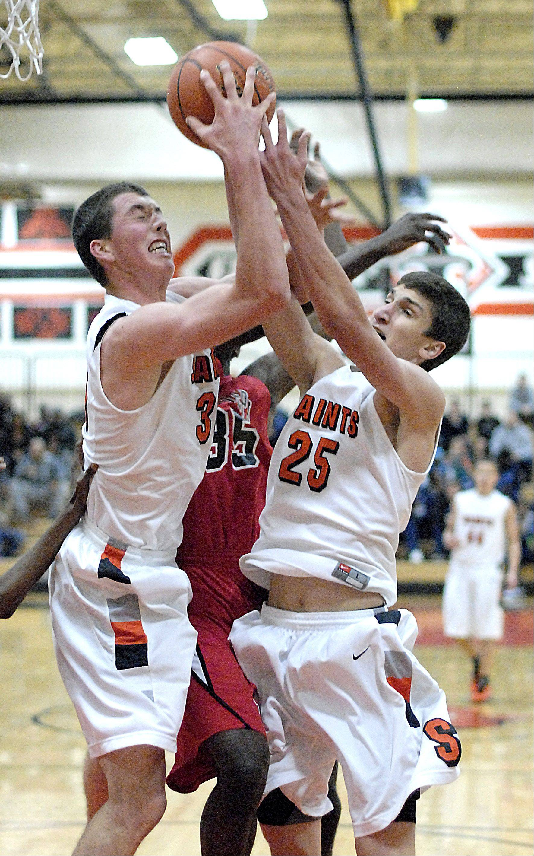 St. Charles East�s David Mason and Dan Wilkerson sandwich St. Joseph�s Karriem Simmons as they fight for a rebound in the first quarter on Friday, November 23.