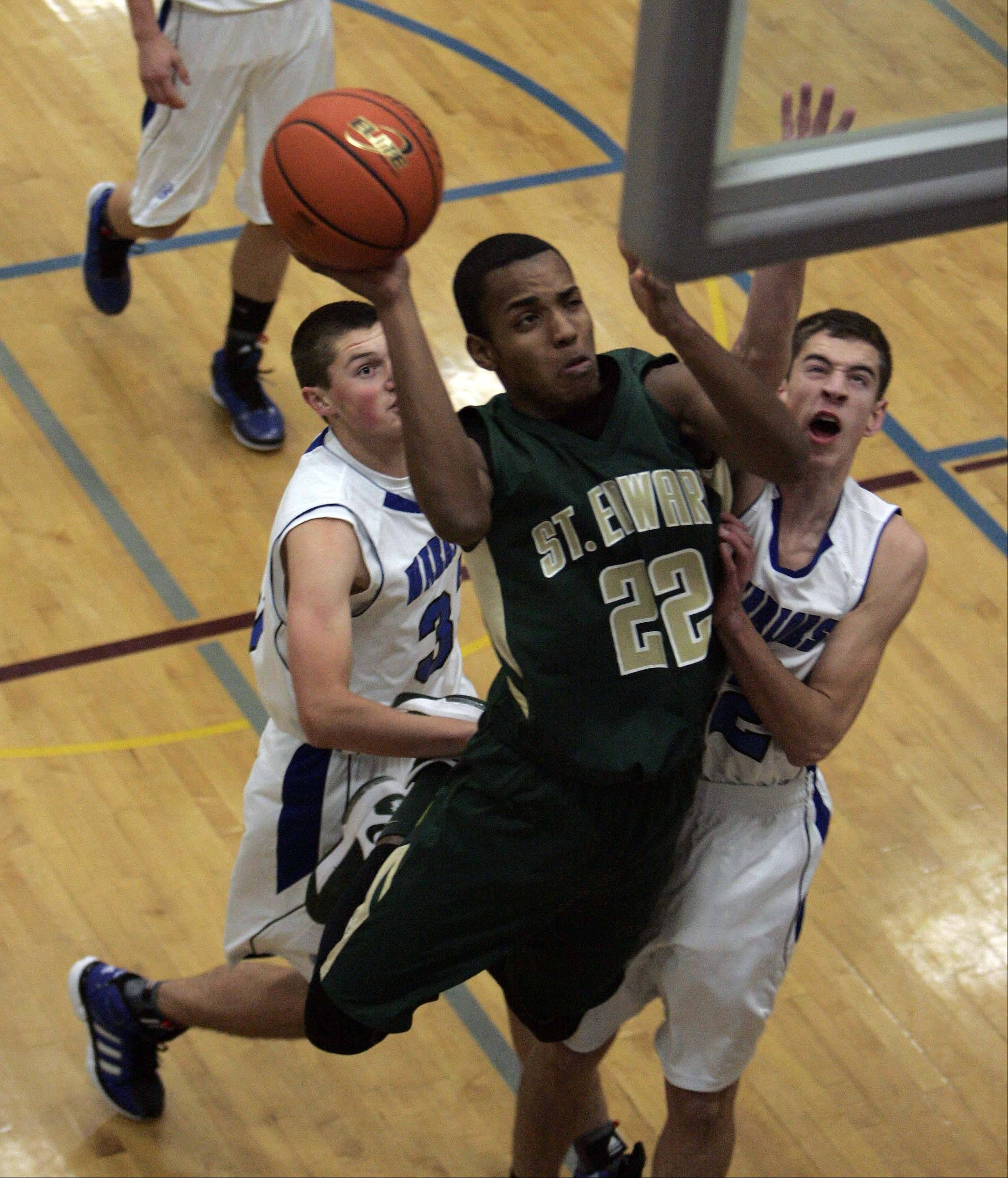 St. Edward forward Adrian Ponce (22) slips through Westminster Christian�s Robert Kleczynski (33) and Colin Brandon (42) during the 6th Annual Warrior Thanksgiving Basketball Classic in Elgin Friday.