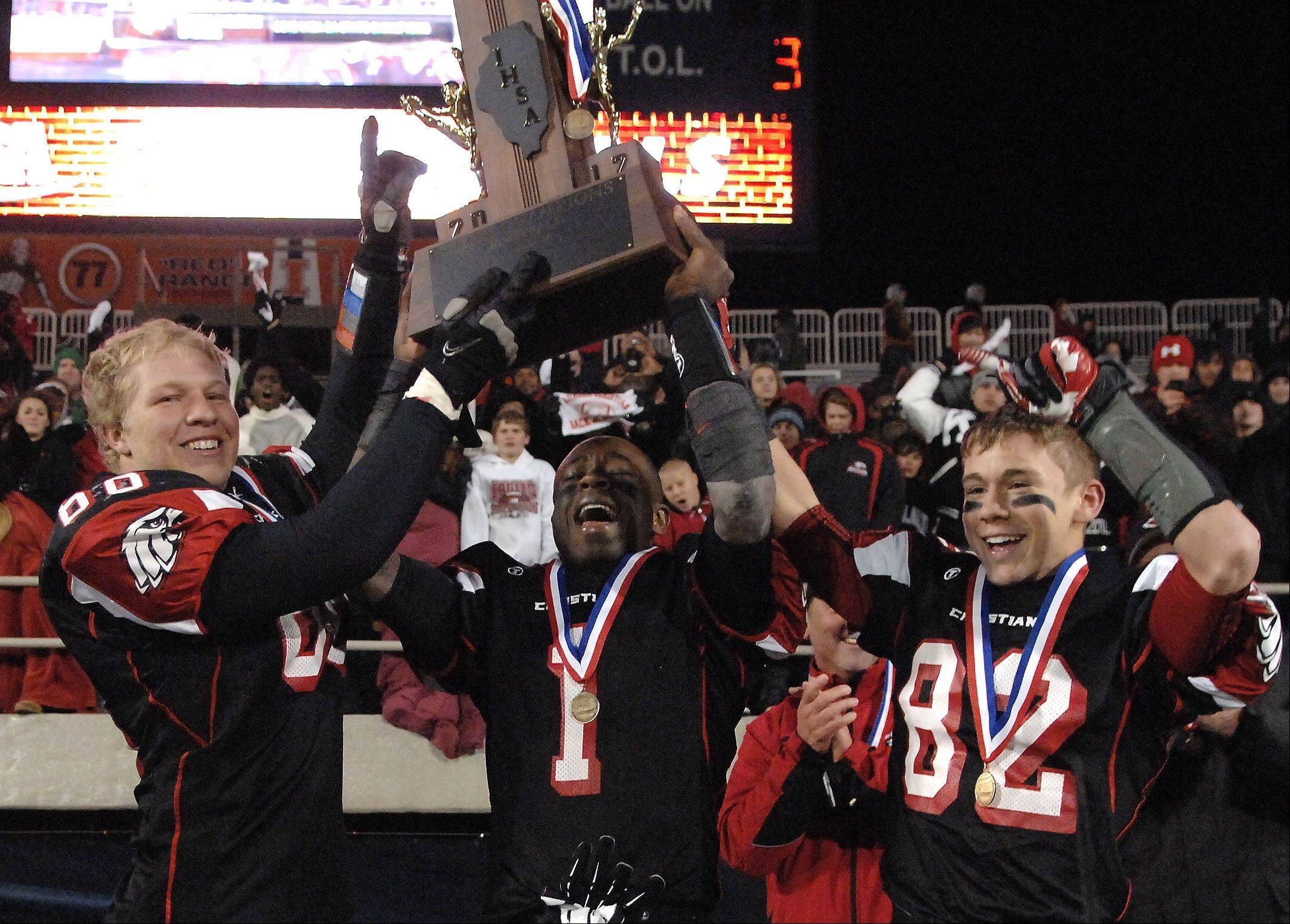 Aurora Christian captains Josh Kok, left, Brandon Mayes and Chad Beebe hold up the championship trophy after their win over Tolono Unity during Friday's Class 3A state championship game at Memorial Stadium in Champaign.
