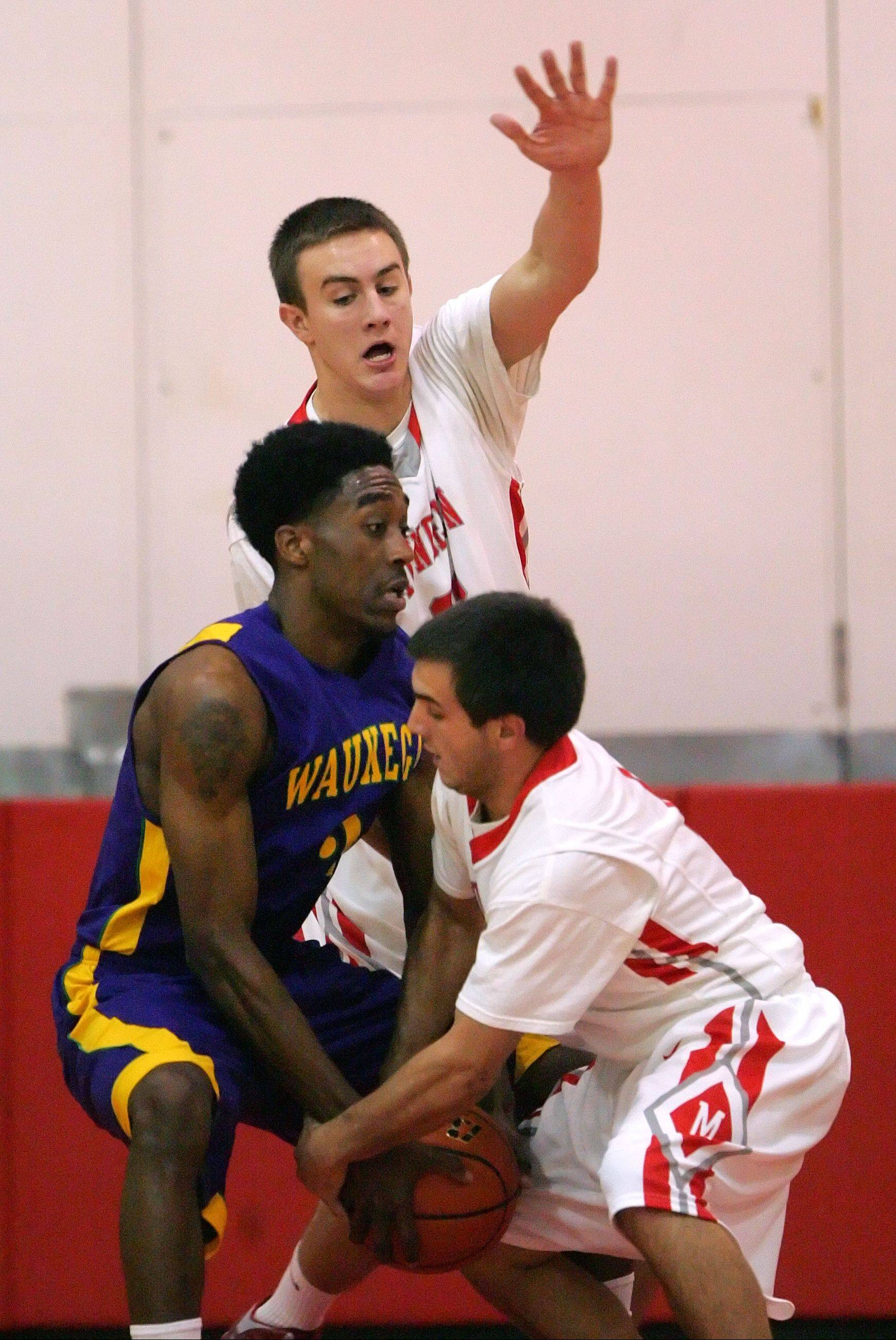 Mundelein's Sean O'Brien, back, and Thomas Gandolfi apply some tough defense against Waukegan's Cornell Fort on Friday night at Mundelein.