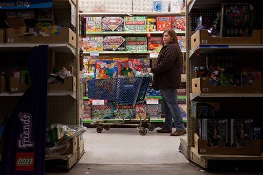 "A customer examines shelves of toys during Toys ""R"" Us' Black Friday sales event in Flint, Mich. on Thursday, Nov. 22, 2012"