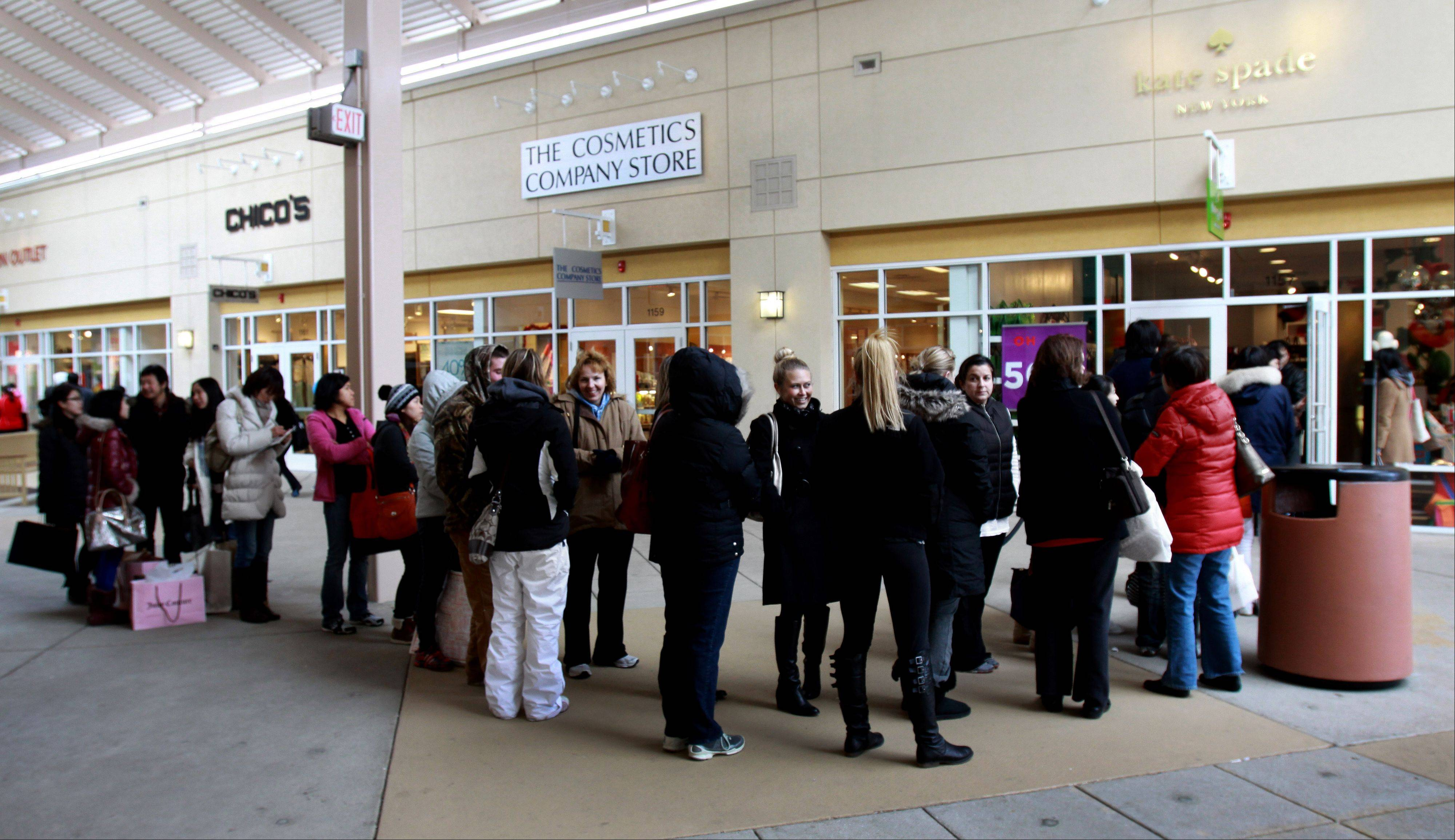 A line forms outside the Kate Spade store at Premium Outlet Mall in Aurora on Friday.