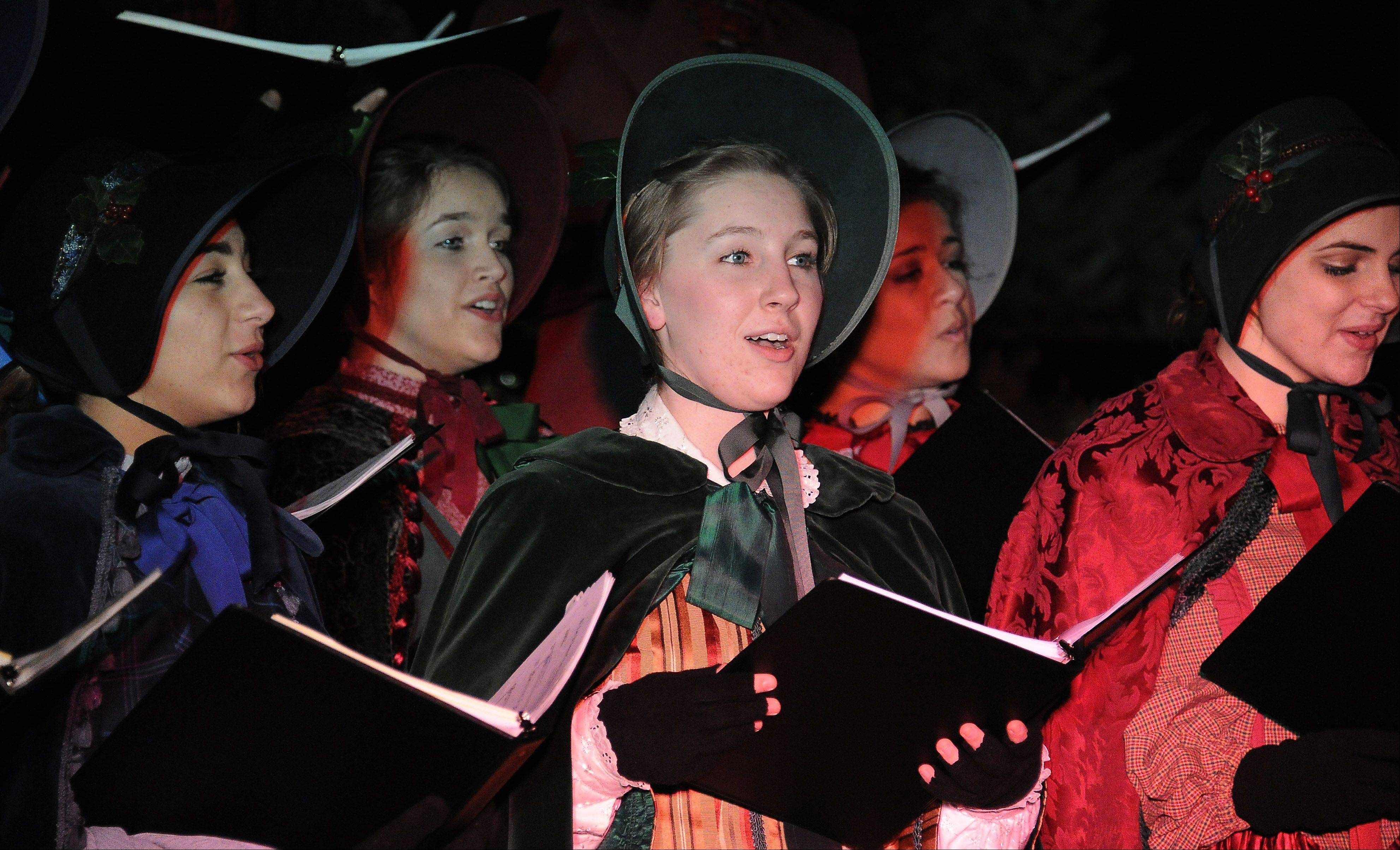 Katie Busse, center, and other Charles Dickens carolers from Hersey High School sing Christmas songs Friday at Arlington Heights' annual tree-lighting festival at North School Park.