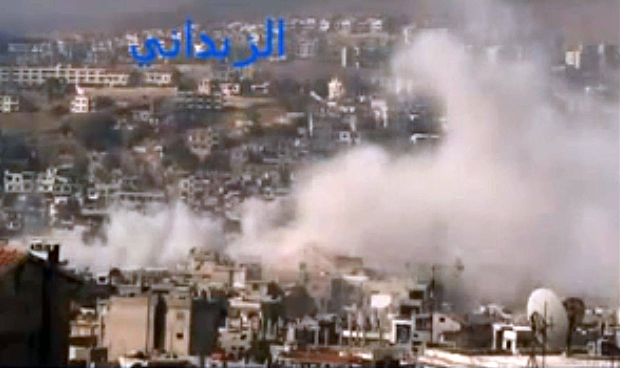 In this image taken Friday from video obtained from the Shaam News Network, which has been authenticated based on its contents and other AP reporting, smoke rises from buildings due to government shelling in the Damascus suburb of Zabadani, Syria. At the same time, Syrian forces are raiding another neighborhood showing how fighting is spreading in Damascus, once a stronghold of President Bashar Assad.