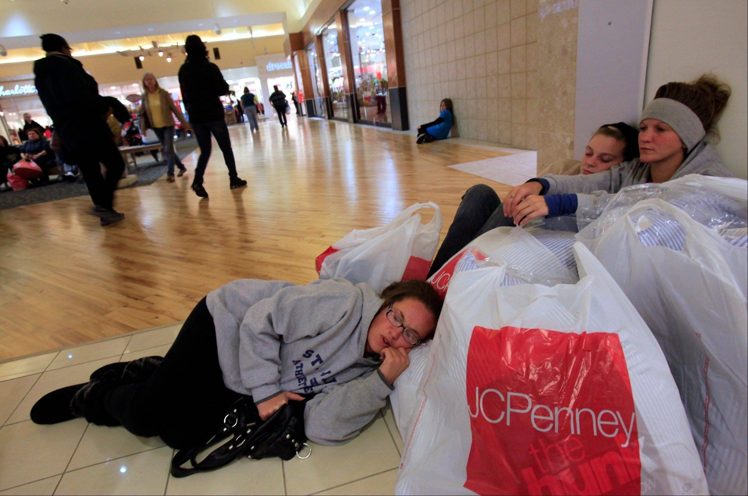 Jessica Wood, right, and fellow shoppers Tami Formont, left, and Courtney Owens wait for others in their group outside JC Penney during Black Friday sales, Friday, Nov. 23, 2012 at Coastal Grand Mall in Myrtle Beach, S.C.