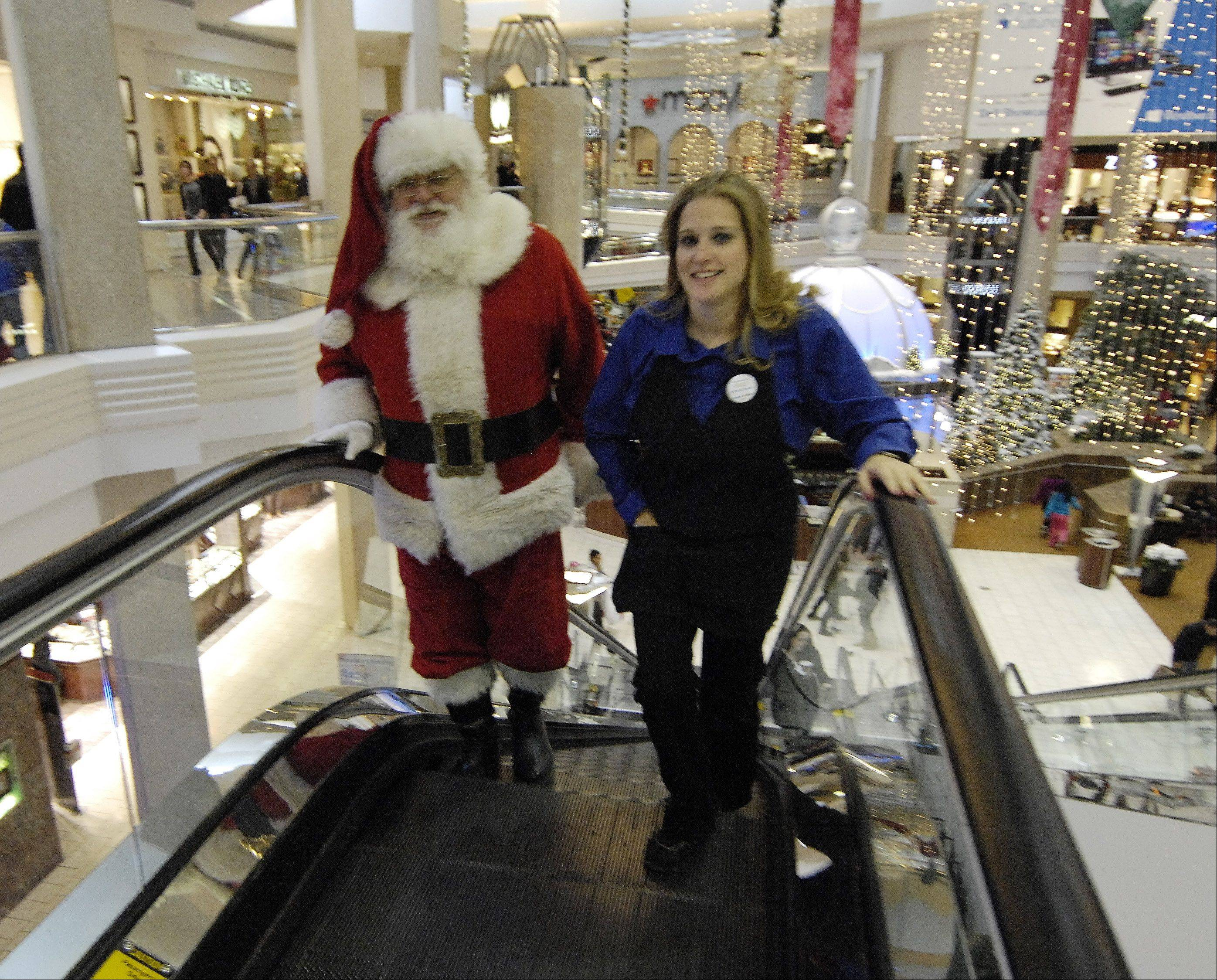 Santa Claus rides the escalator to the second level at Woodfield Mall in Schaumburg on Black Friday.