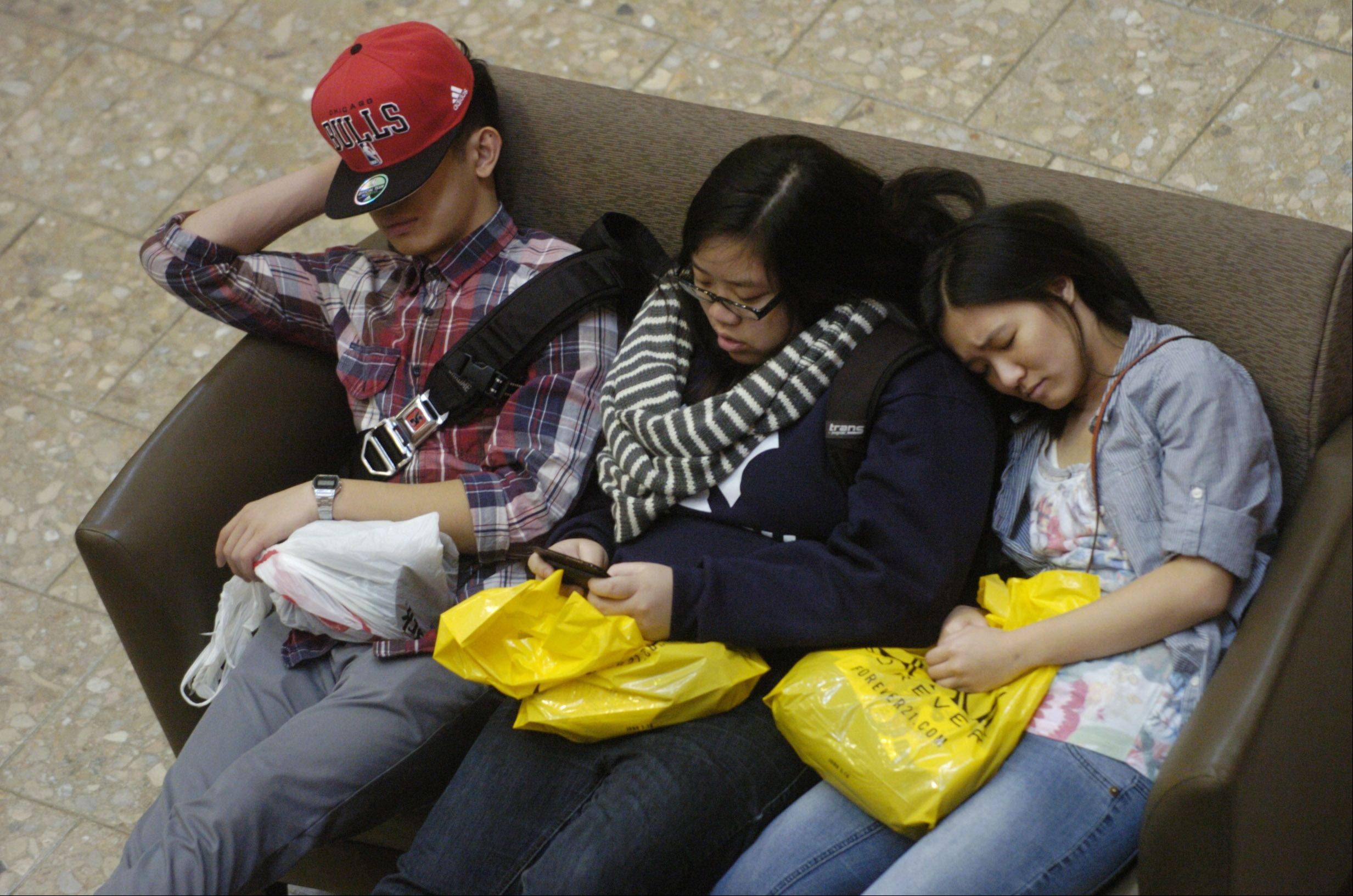 Shoppers relax on the couch outside of Macy's at Woodfield Mall in Schaumburg during the morning of Black Friday.