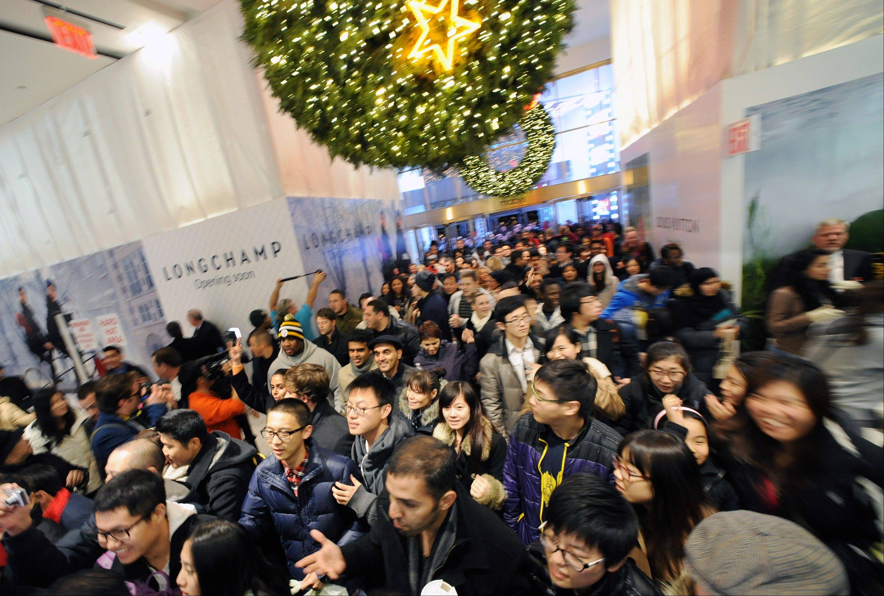 Shoppers rush through the doors at a Macy's Inc. store in New York, U.S., on Friday, Nov. 23, 2012.