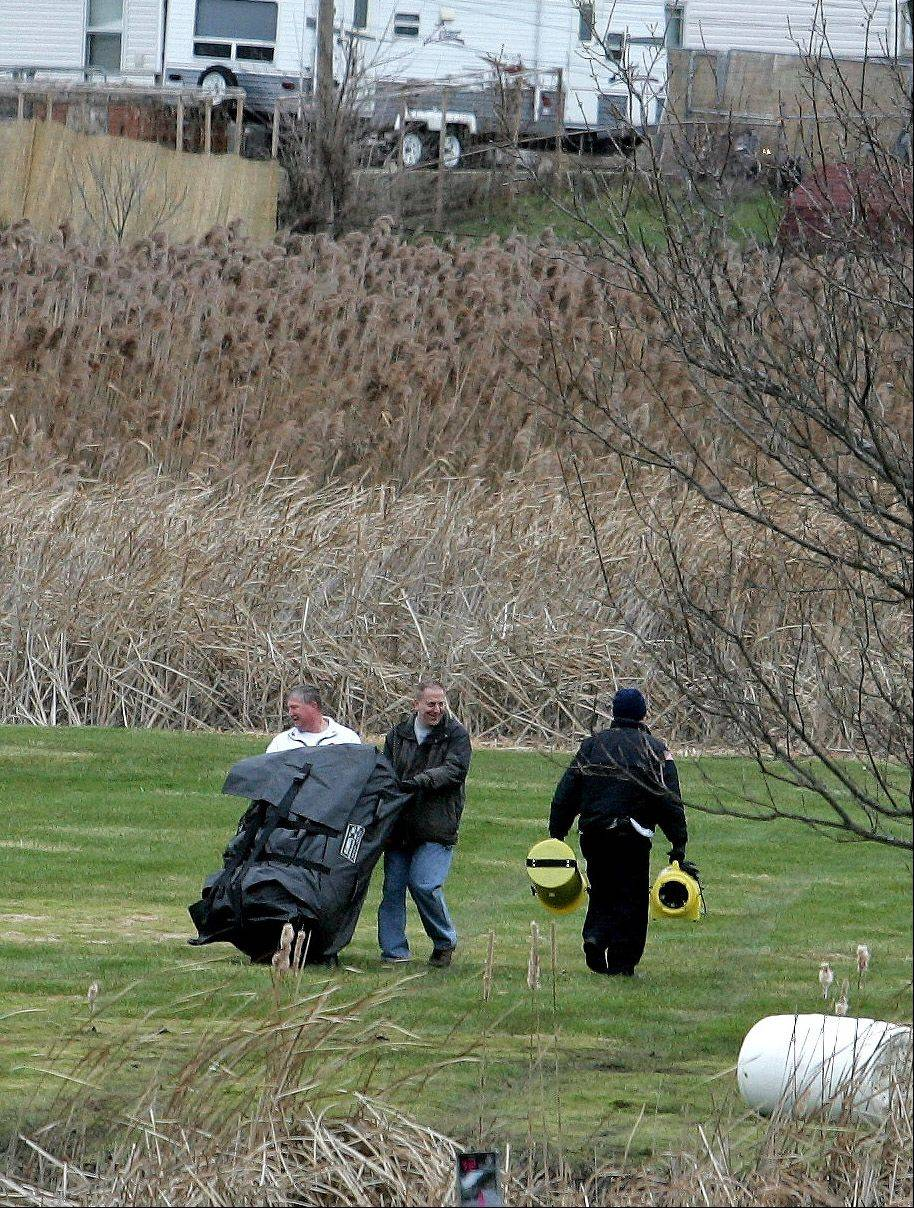 On Friday, police carry equipment into the park after the body of Rachel Morris was discovered there Thursday.