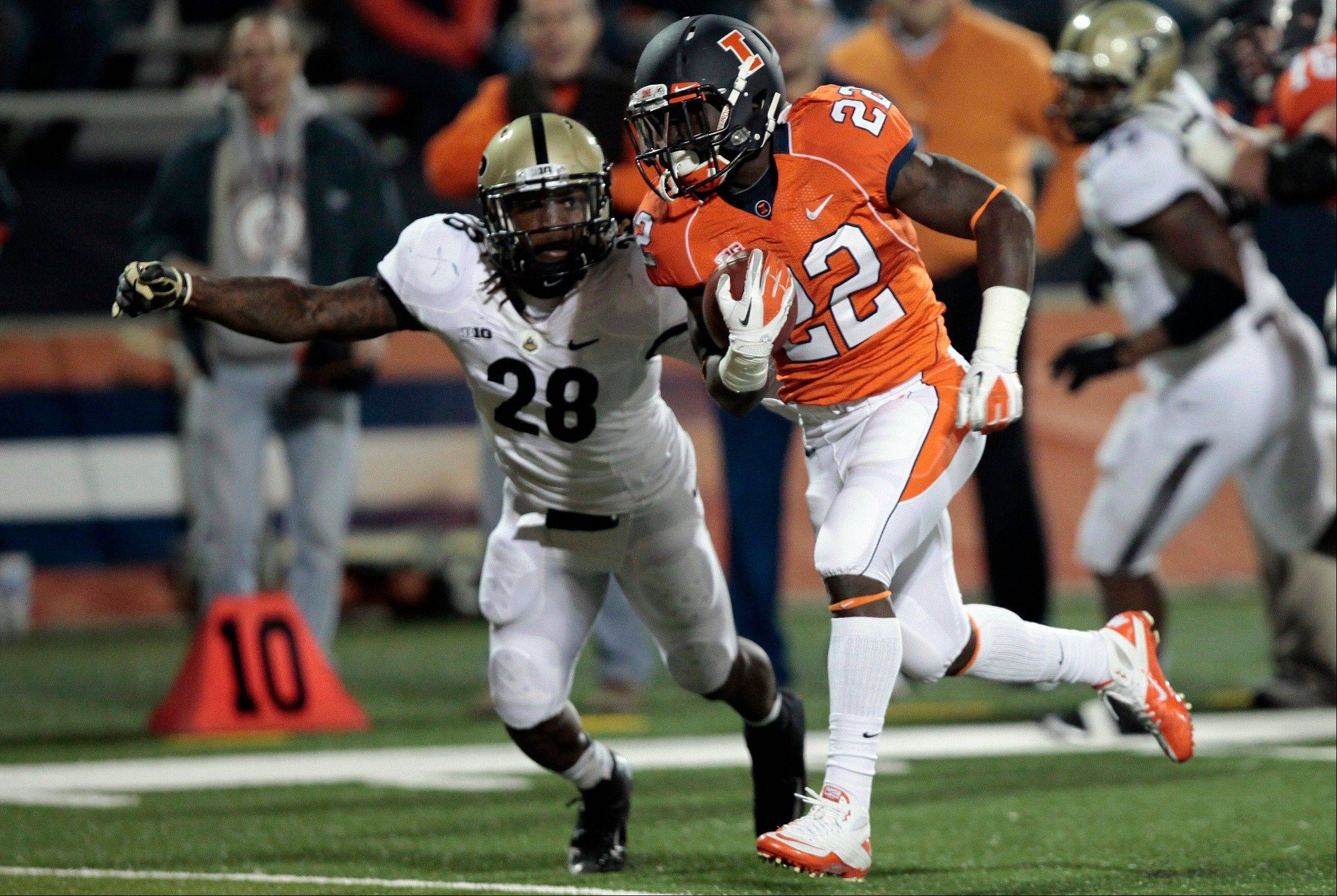 Illinois' Dami Ayoola runs the ball into the end zone past Purdue's Josh Johnson during the second half in Champaign.