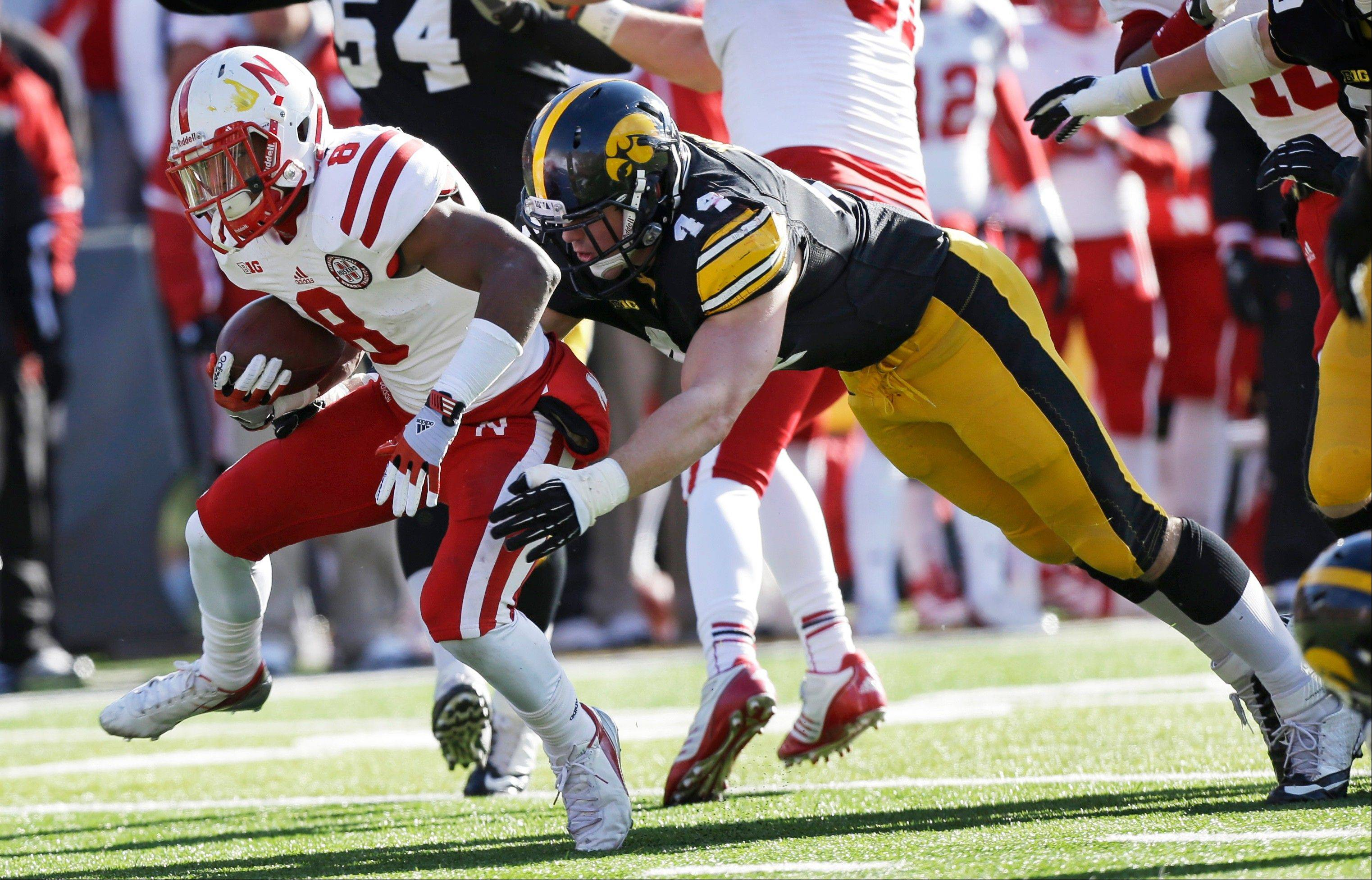 Nebraska running back Ameer Abdullah tries to break a tackle by Iowa linebacker James Morris Friday during the first half in Iowa City. Nebraska beat the Hawkeyes 13-7.