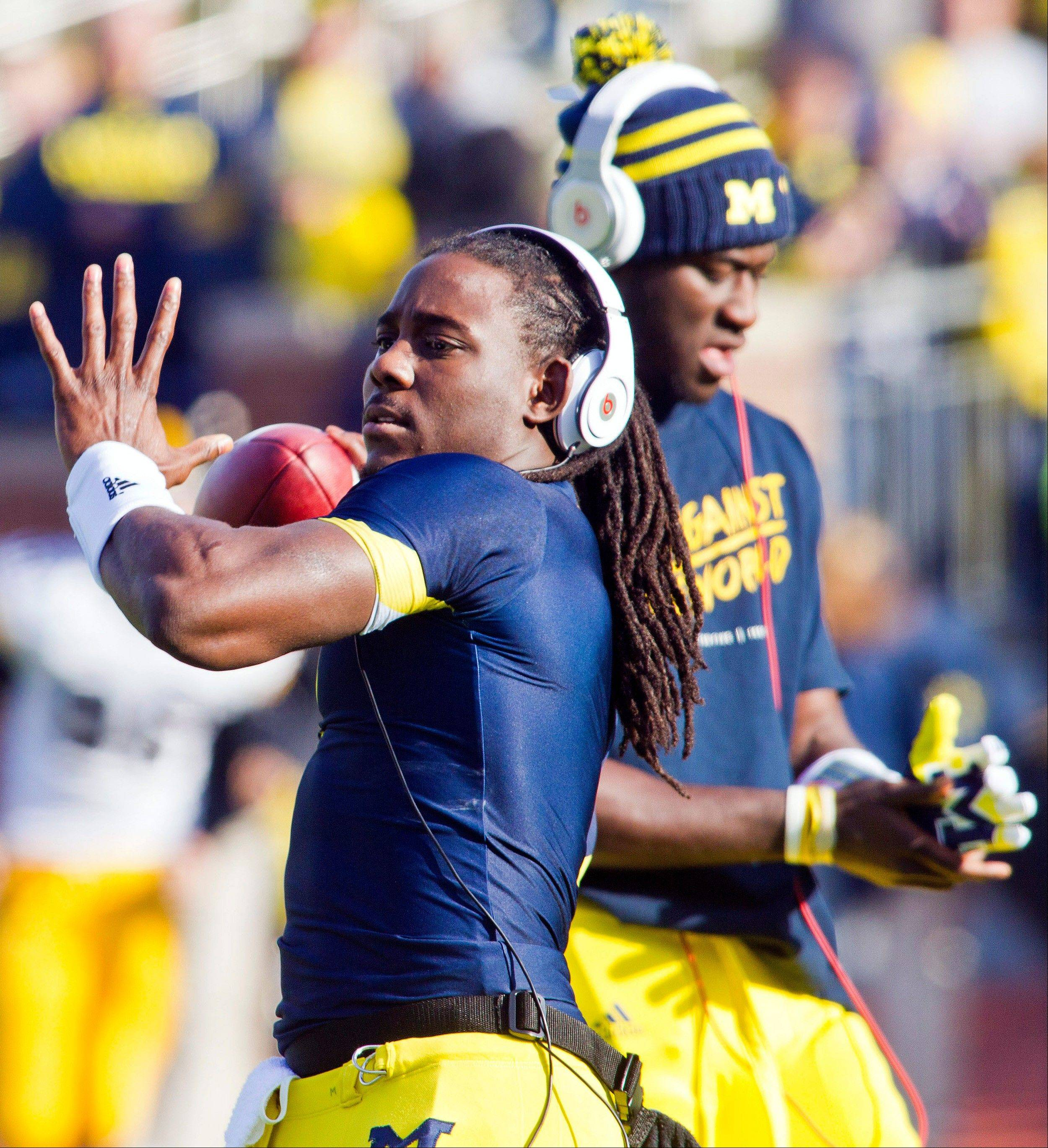 Michigan quarterback Denard Robinson, front, warms up beside fellow quarterback Devin Gardner before a game. Robinson could see action at tailback on Saturday as the Wolverines take on unbeaten Ohio State.