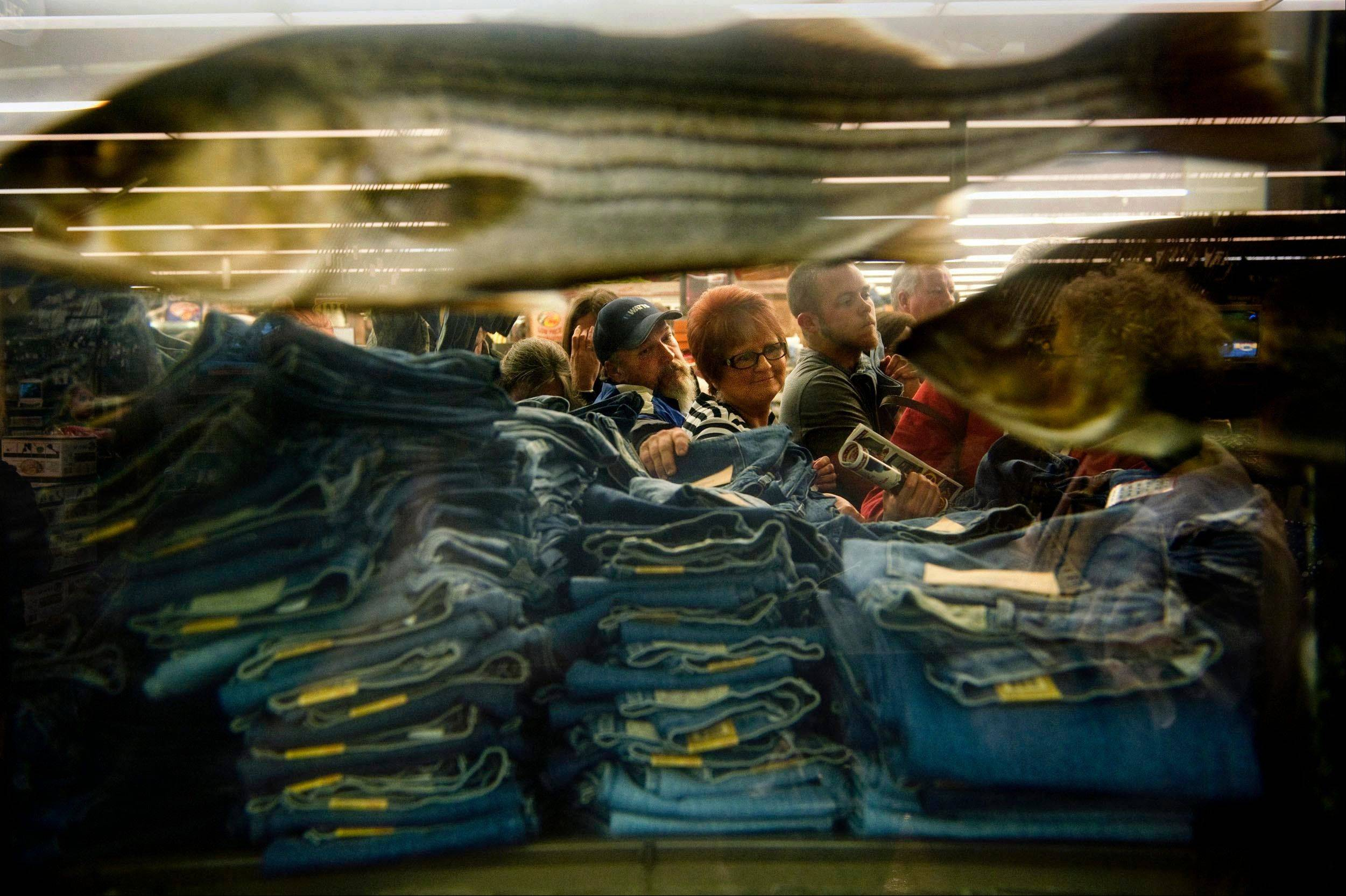Shoppers pick through stacks of discounted jeans beside a giant aquarium inside Bass Pro Shops after the doors opened at 5 a.m., kicking off �Black Friday� and the holiday shopping season in Memphis, Tenn.