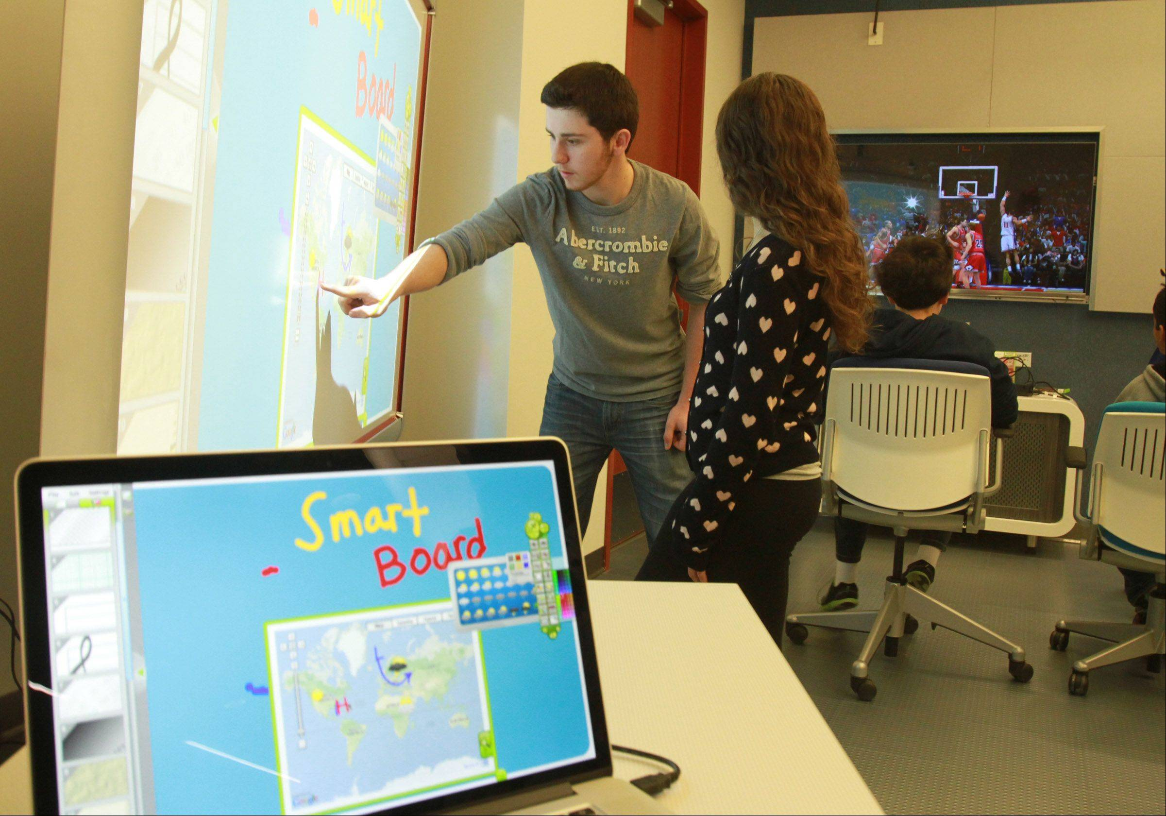 Chris Napier, 16, and Lisa Mancuso, 17, both of Schaumburg, work on a SMART Board screen Saturday in Schaumburg Township District Library�s Teen Place in Schaumburg.