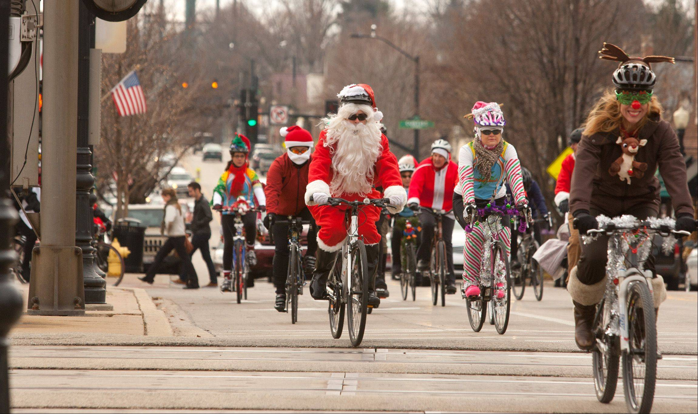 Members of the Pedalheads cycling club ride Saturday morning on Main Street in downtown Downers Grove toward Good Samaritan Hospital, wearing Santa suits to deliver gifts to hospitalized children. Vicky Tate, right, leads the group.
