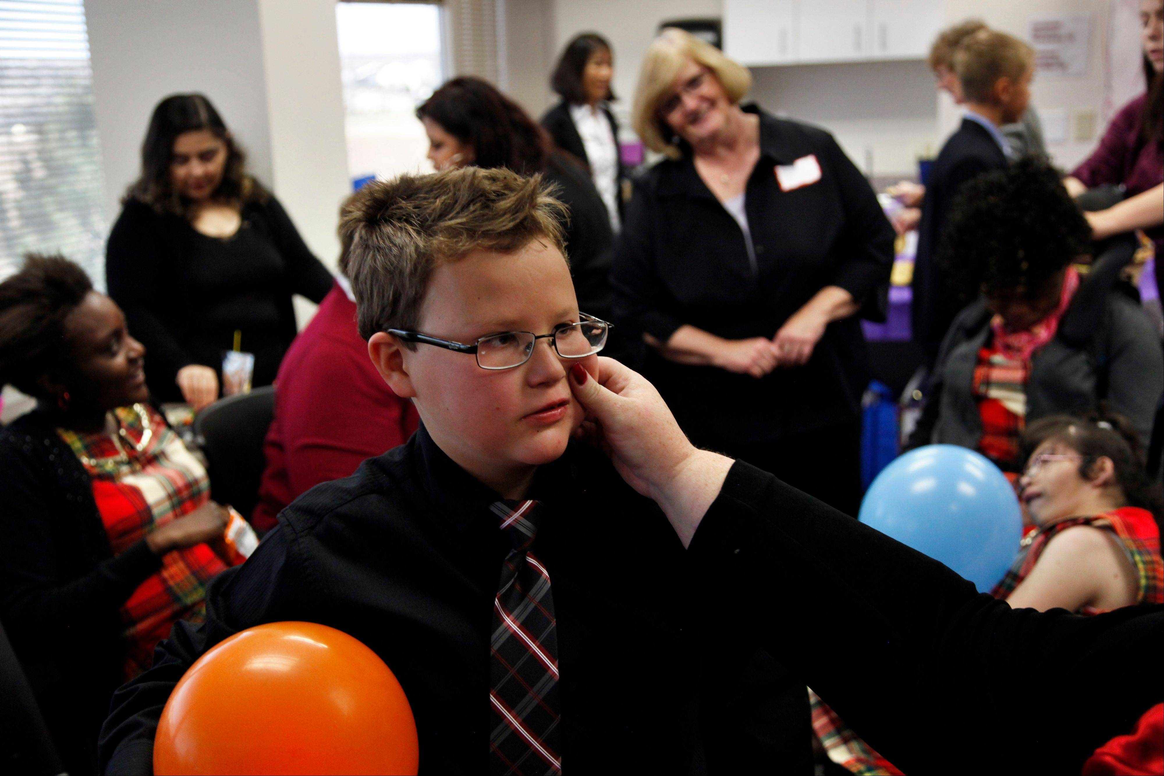 Anthony, 11, the intellectually-disabled son of Carrie Ann Lucas, gets a pinch on the cheek from his mother during a party held for newly-adopted children and their families on National Adoption Day at the Arapahoe County Justice Center in Centennial, Colo., on the day Anthony officially became her son. Carrie Ann Lucas, herself disabled, is the mother of four disabled adopted children.