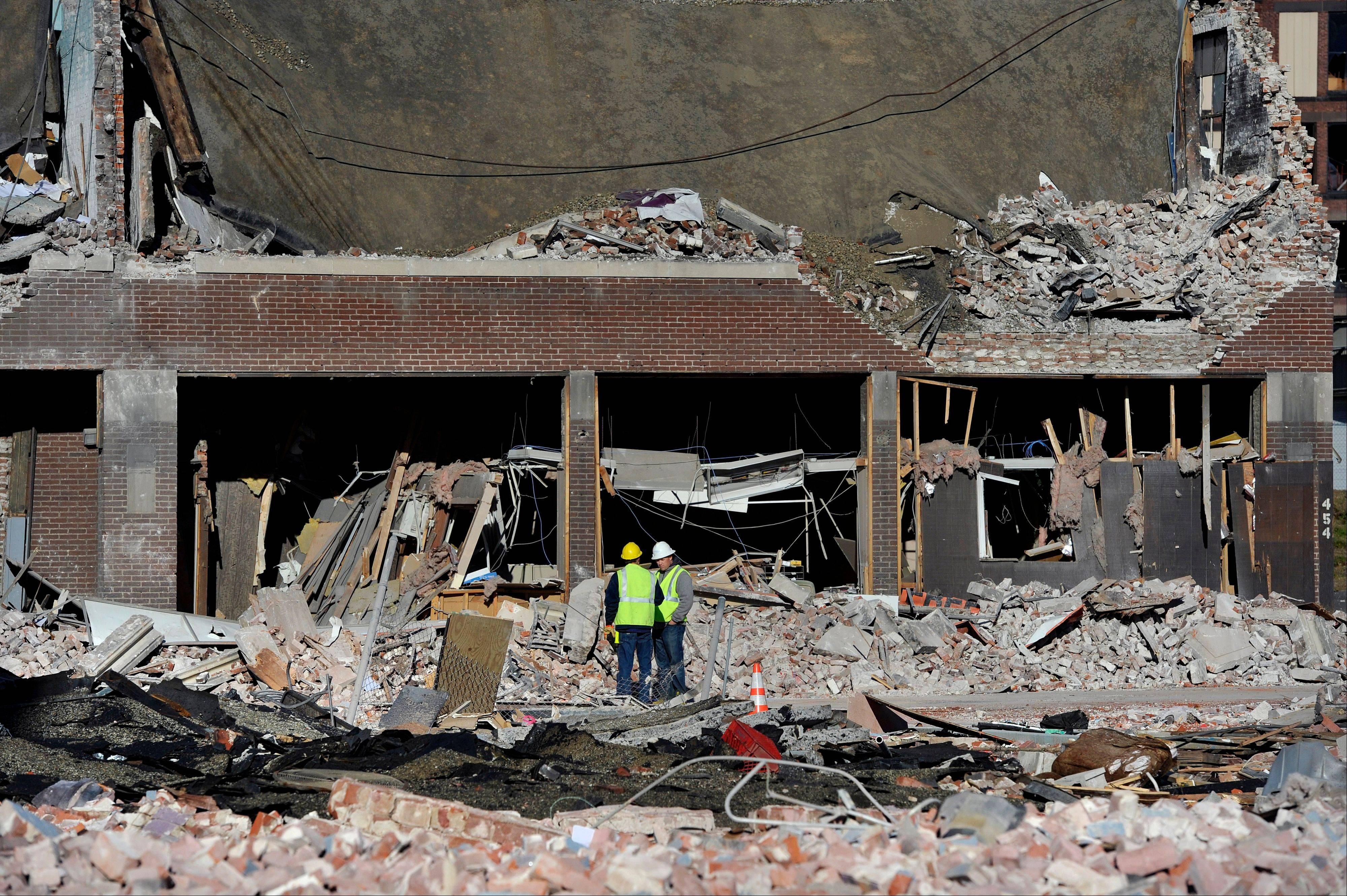 Inspectors stand in debris, Saturday, at the site of a gas explosion that leveled a strip club in Springfield, Mass.