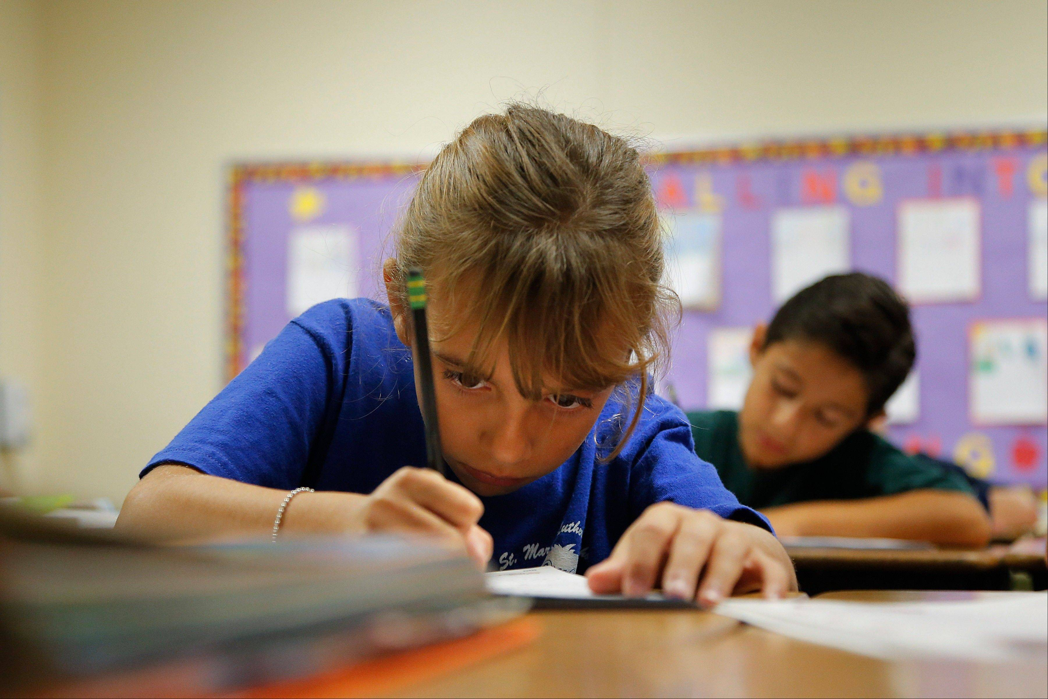 Alexia Herrera practices writing in cursive Thursday at St. Mark�s Lutheran School in Hacienda Heights, Calif.