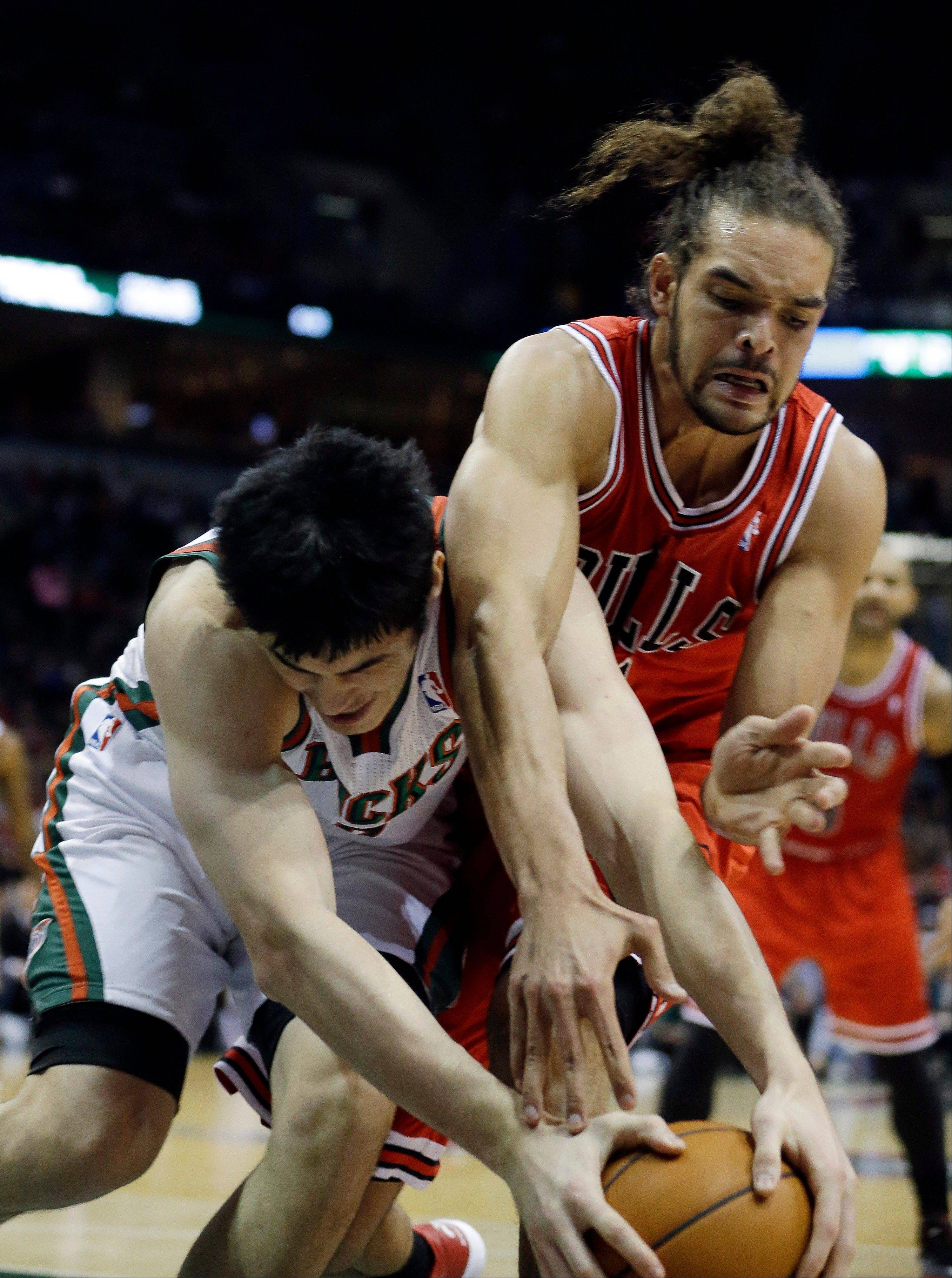The Bulls� Joakim Noah, right, battles the Bucks� Ersan Ilyasova battle for the loose ball Saturday night at Milwaukee.