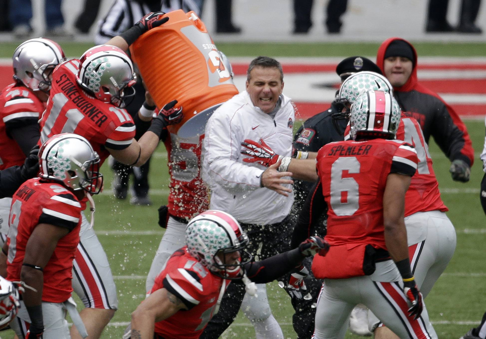 Ohio State head coach Urban Meyer, center, gets doused by senior wide receiver Jake Stoneburner (11) Saturday after a 26-21 win over Michigan in Columbus, Ohio.