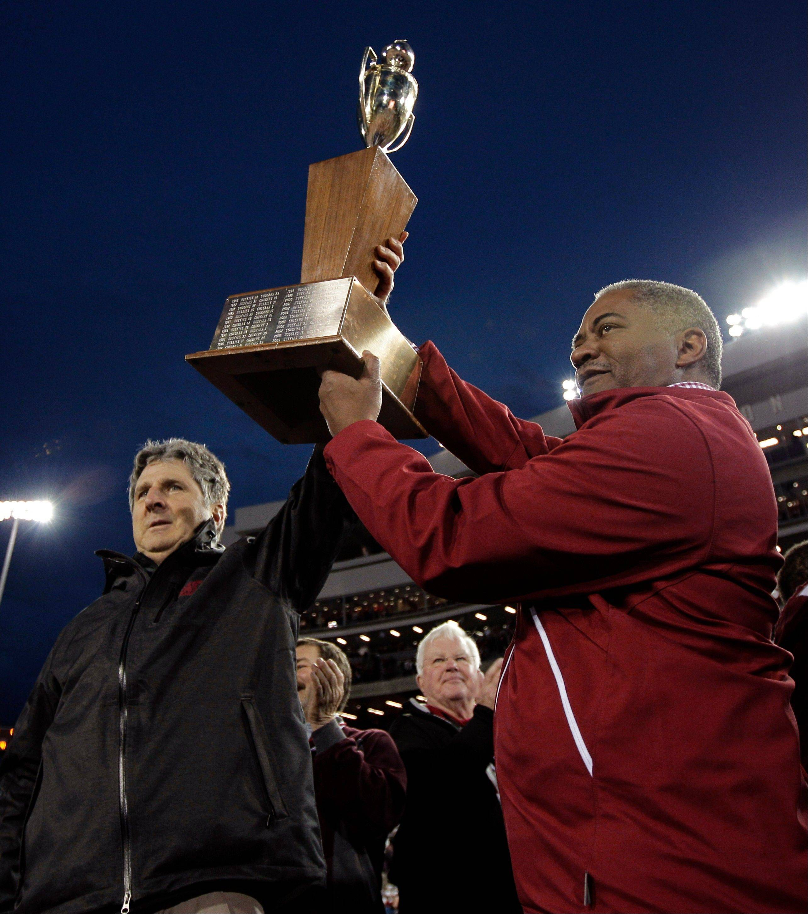 Washington State head coach Mike Leach, left, and Washington State President Elson Floyd, right, lift the Apple Cup trophy Friday after defeating Washington 31-28 in overtime in Pullman, Wash.