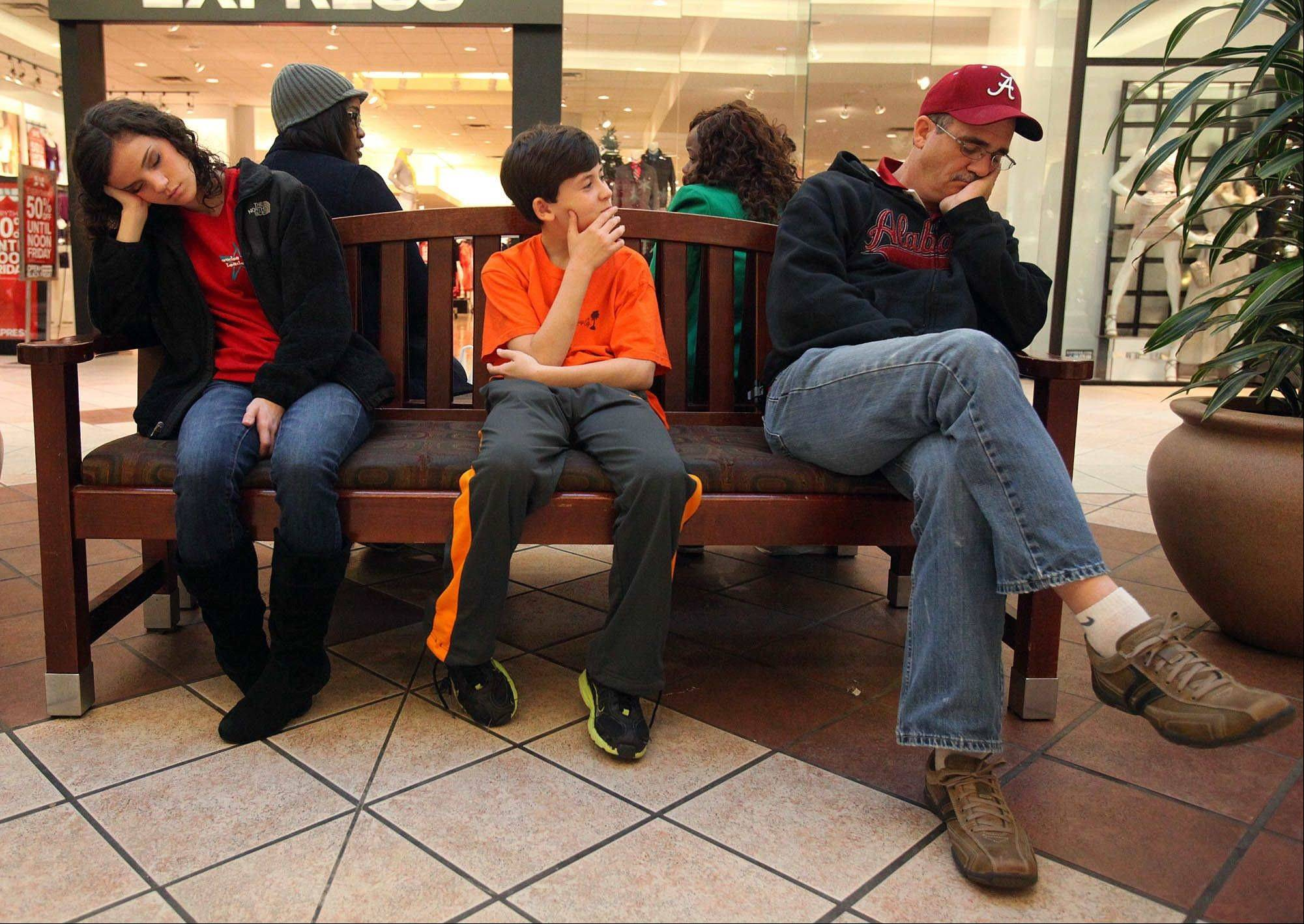 Black Friday shoppers Victoria McDaniel, 16, left, and Ronnie McDaniel, right, sleep as Connor Church, 12, center, gets a laugh at the University Mall in Tuscaloosa, Ala.