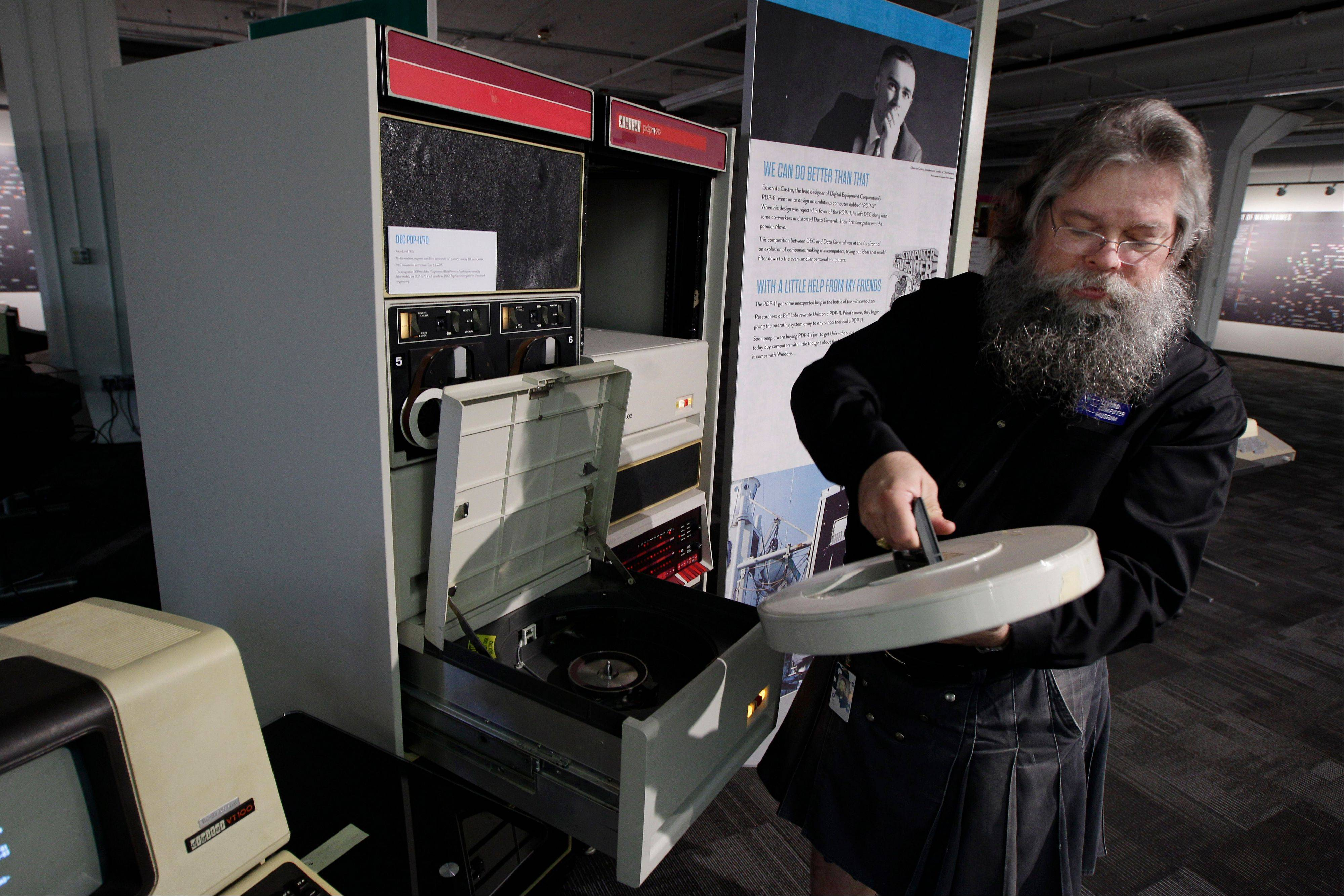 Ian King, senior vintage systems engineer at the Living Computer Museum in Seattle, loads a large disk drive into a working DEC 11/70 minicomputer from 1975. The machine is part of the collection of running computers at Paul Allen's newly opened Living Computer Museum.