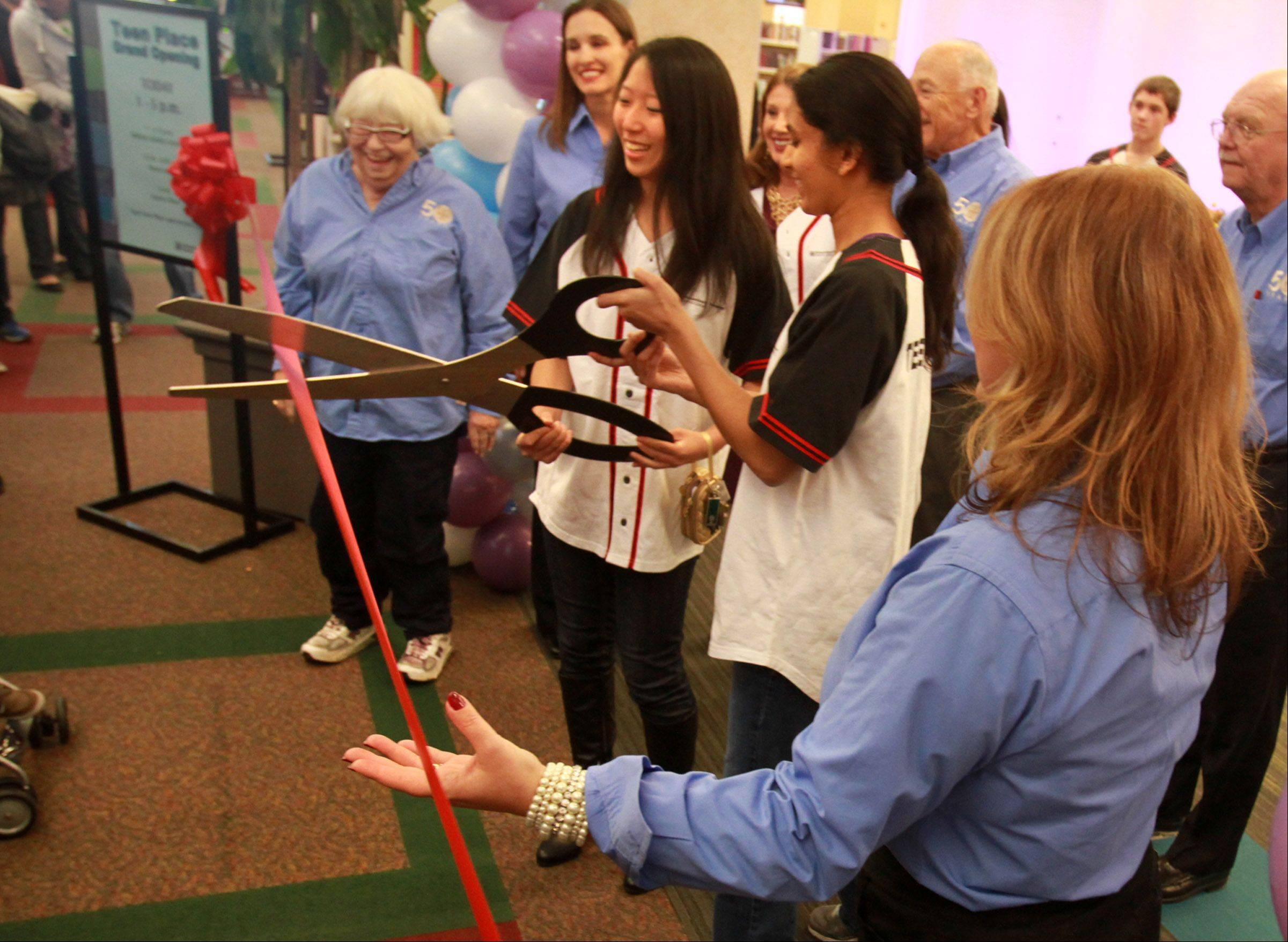 Meran Liu and Avni Baviski, both 18 of Hoffman Estates, cut the ribbon during the grand opening Saturday for the Schaumburg Township District Library's Teen Place inside the library in Schaumburg.