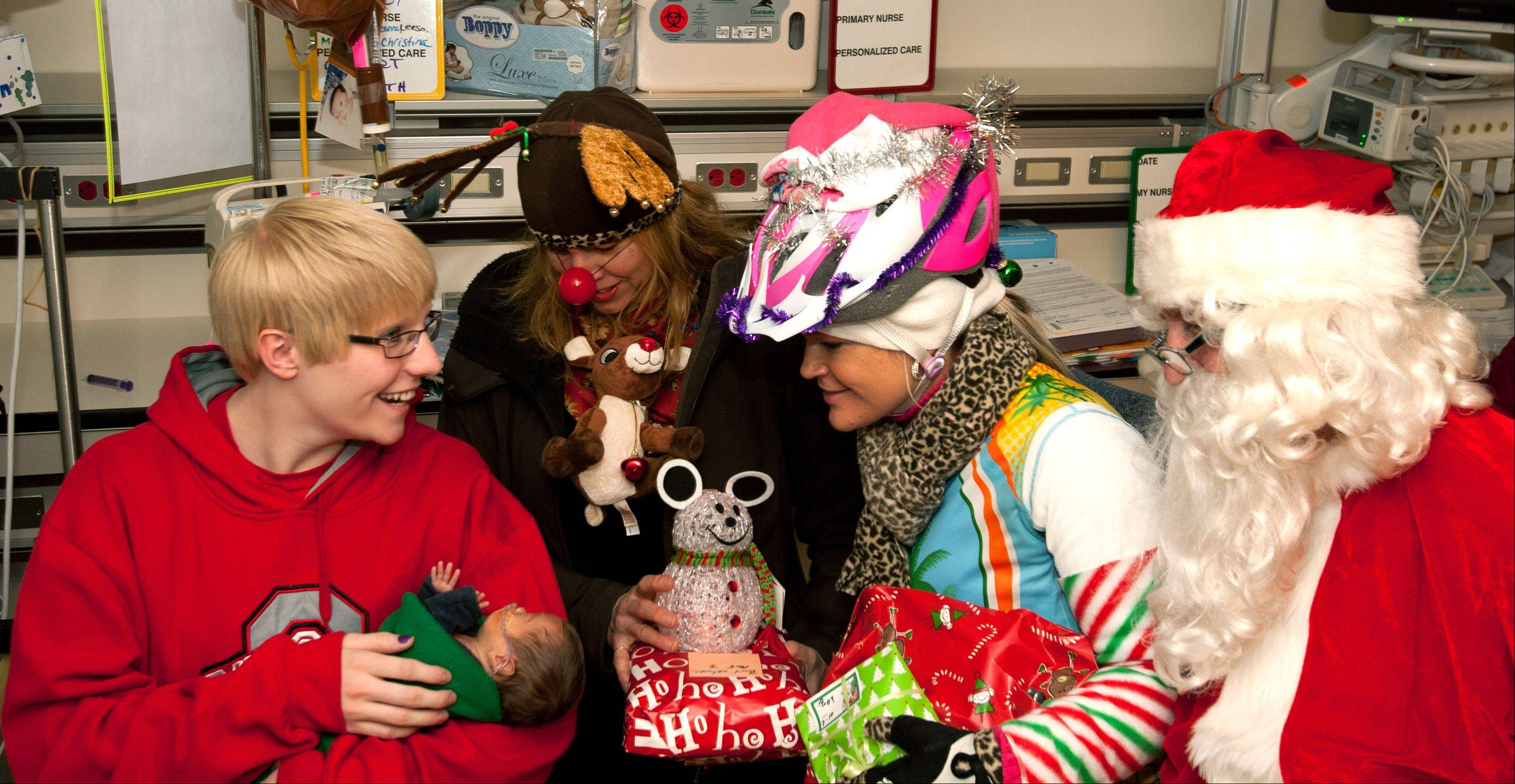 Bridget Vazquez of Naperville and her son Logan, who was born prematurely and remains in neonatal intensive care at Advocate Good Samaritan Hospital in Downers Grove, receive a visit from Pedalheads cycling club members Vicky Tate, Vita Zadura and Todd Crisman on Saturday as the bicyclists delivered gifts to hospitalized children.