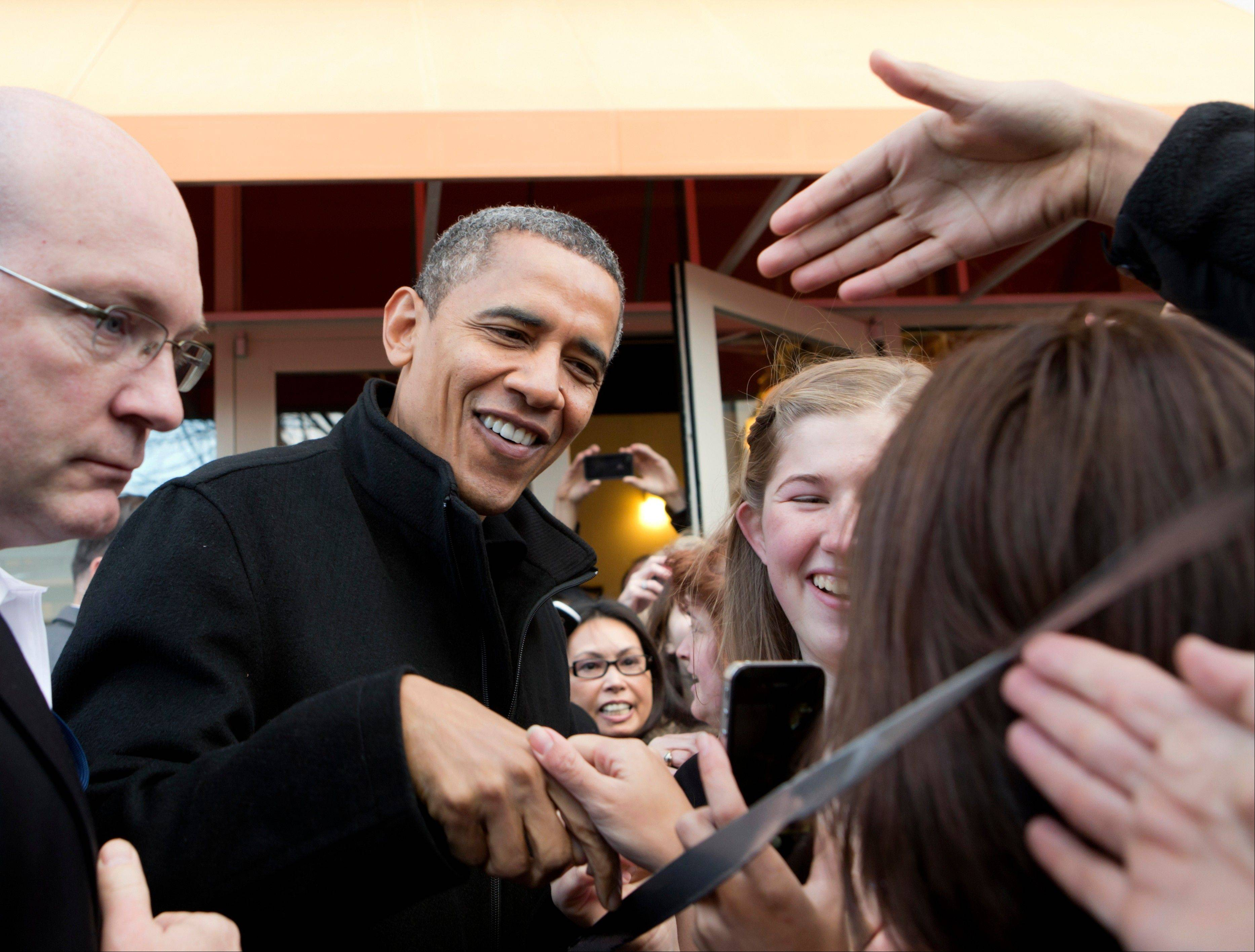 President Barack Obama shakes hands Saturday outside a small bookstore in Arlington, Va.
