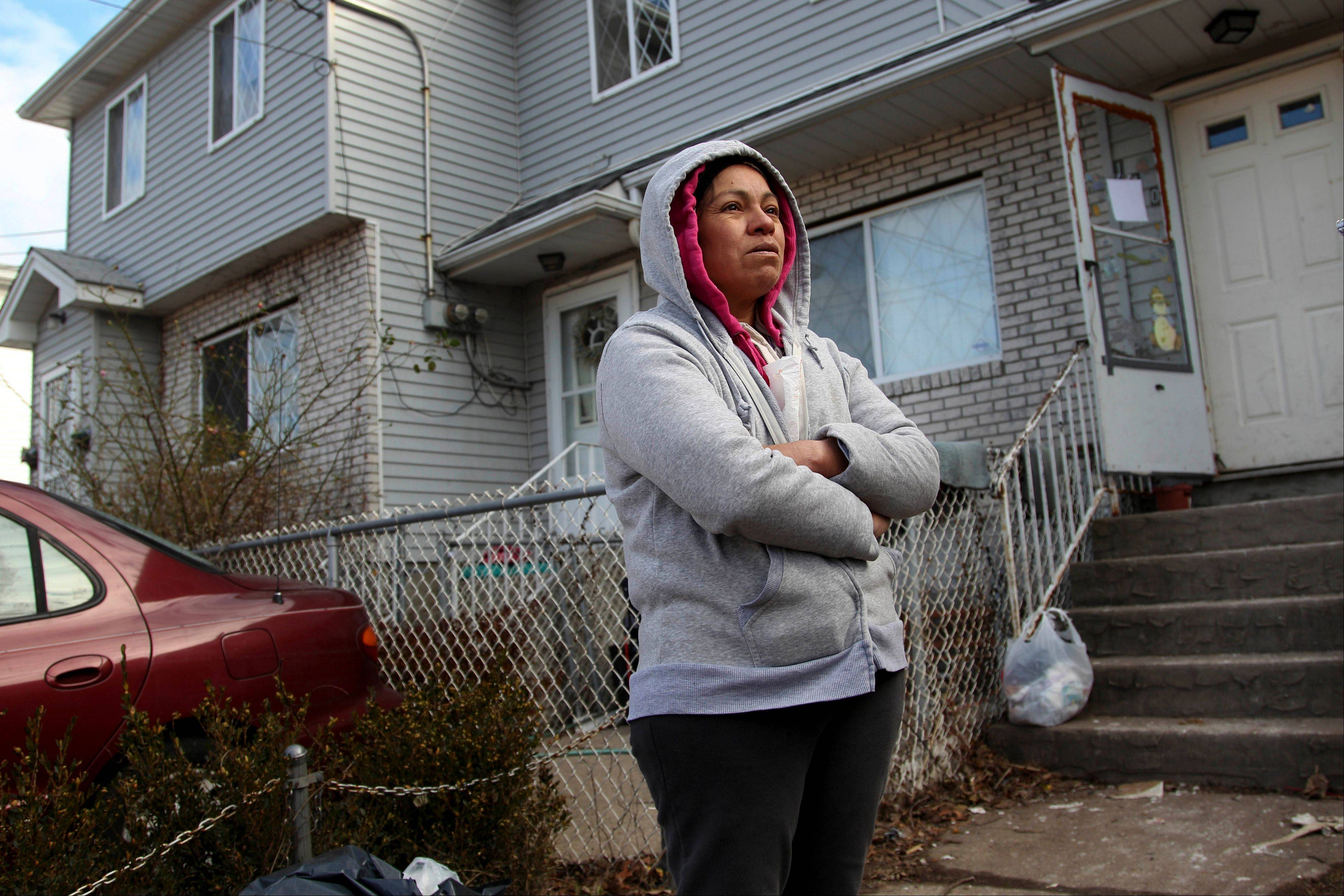 Associated Press/Nov. 14, 2012 Mexican immigrant Maria Lucero stands in front of the home she rented which was damaged by Superstorm Sandy in the Midland Beach section of Staten Island, New York.