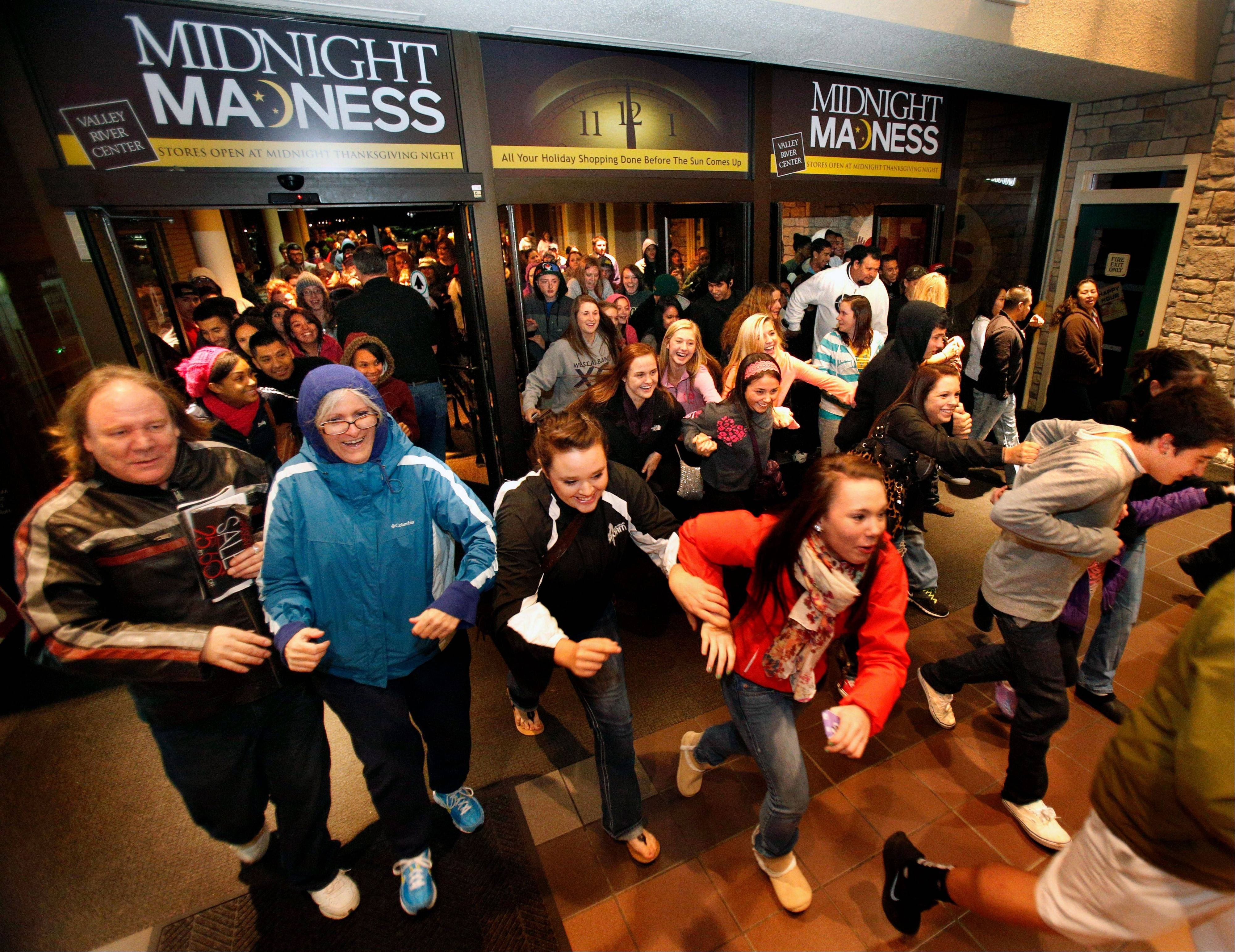 Black Friday shoppers pour into the Valley River Center mall for the Midnight Madness sale Friday in Eugene, Ore.