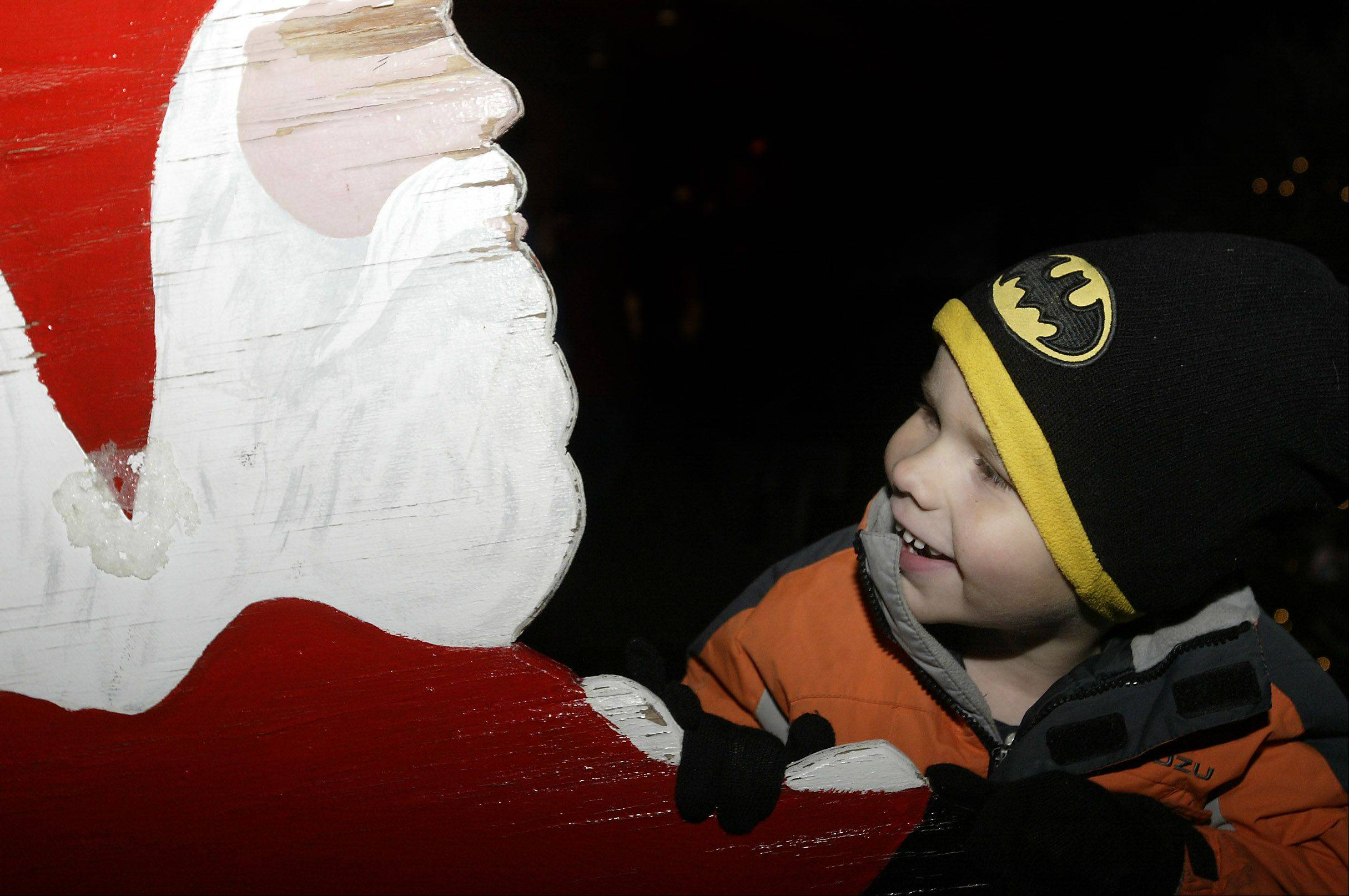Trent Thiem of Batavia examines a wooden Santa during the 2011 Celebration of Lights Festival Sunday in Batavia. This year's festival on Sunday will feature a community singalong, tree lighting ceremony, story hour, visit with Santa and more.